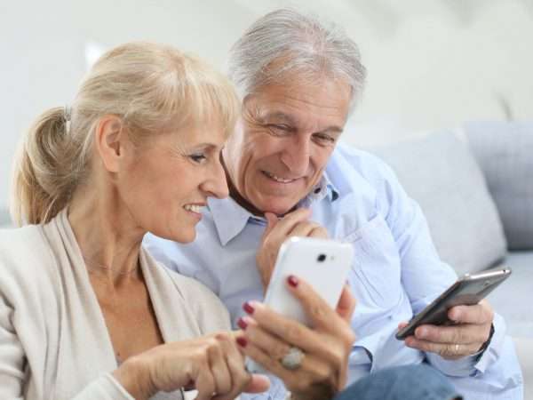 Senior couple at home using smartphone
