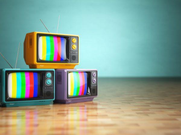38068661 – vintage television concept. stack of retro tv set on green background. 3d