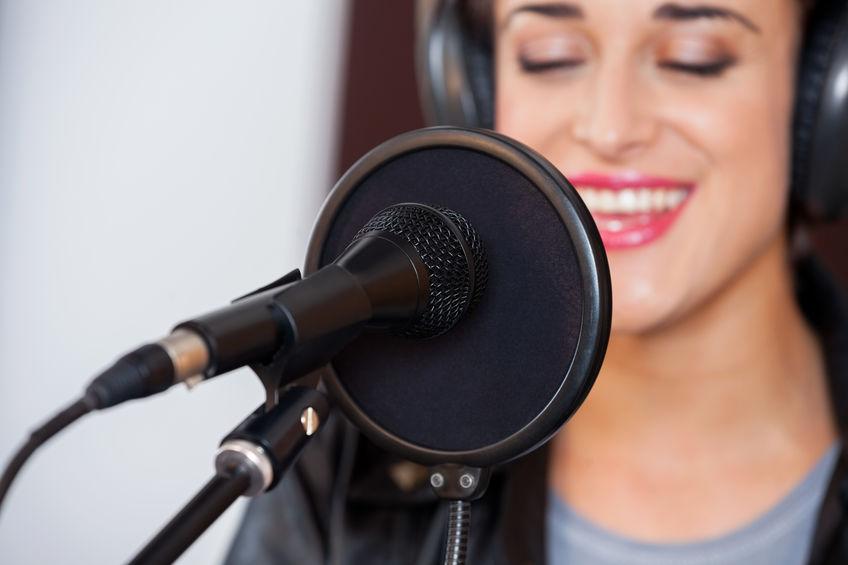 Imagem mostra um microfone em um pedestal em frente a um computador.