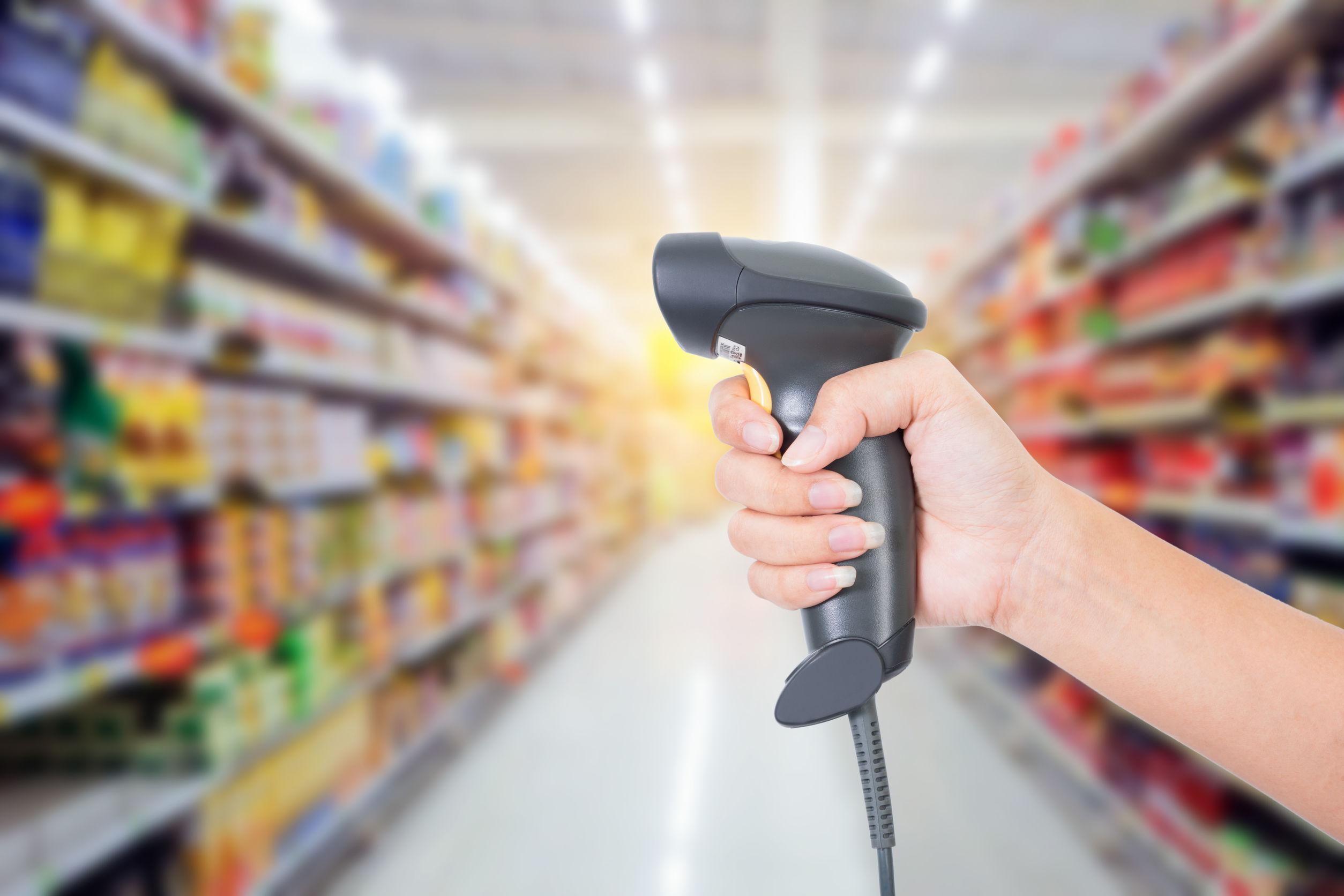 Imagem mostra uma pessoa segurando um leitor de código de barras em um supermercado.