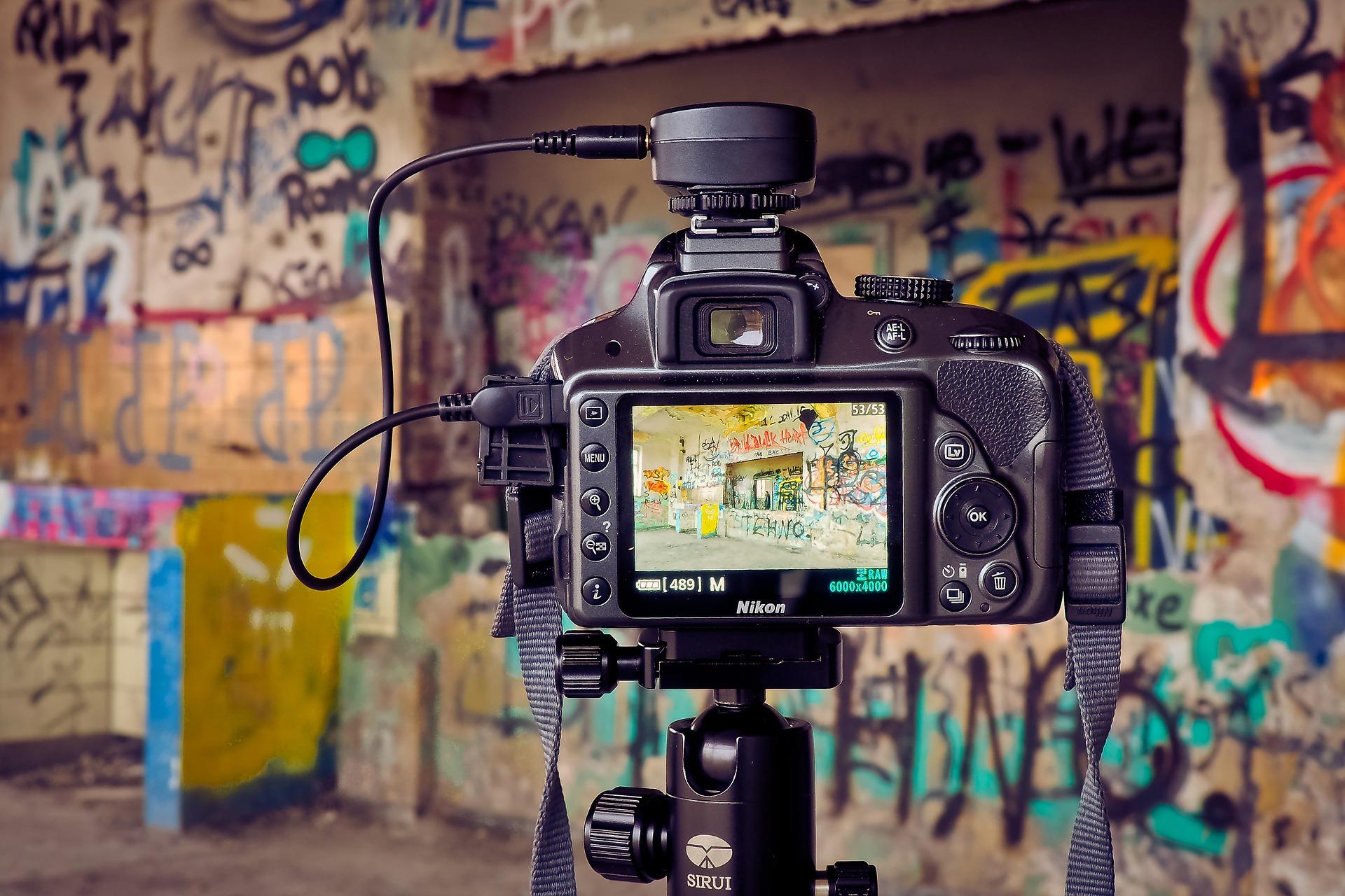 Imagem mostra uma câmera Nikon em um tripé.