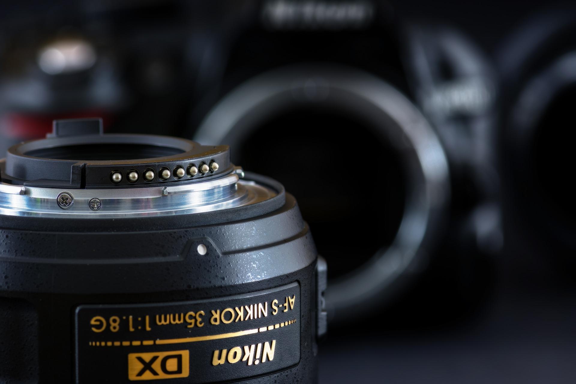 Imagem mostra uma lente em destaque e uma câmera Nikon ao fundo.