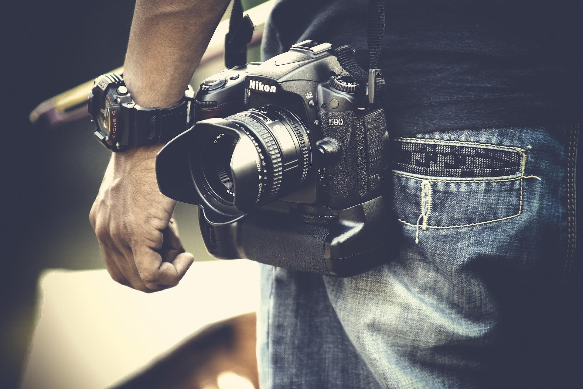 Imagem mostra um homem carregando uma câmera Nikon D90.