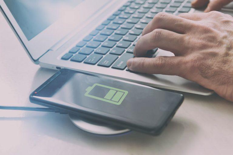 Pessoa teclado no notebook com celular sobre carregador por indução.