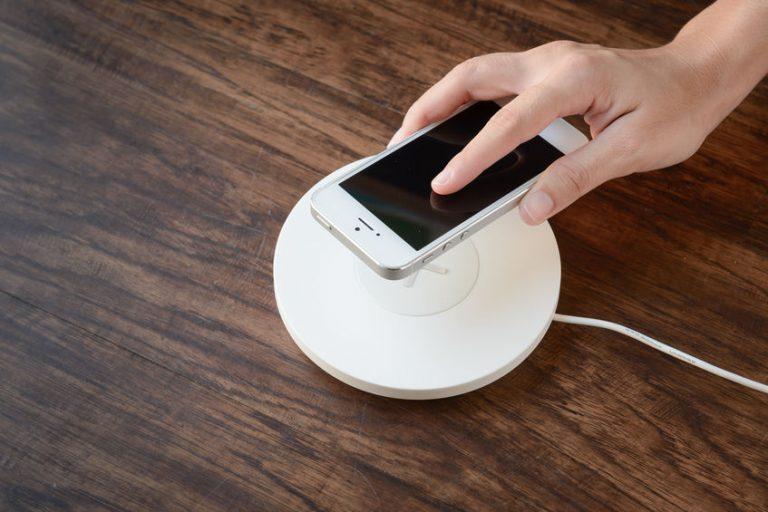 Pessoa aproximando celular do carregador por indução.