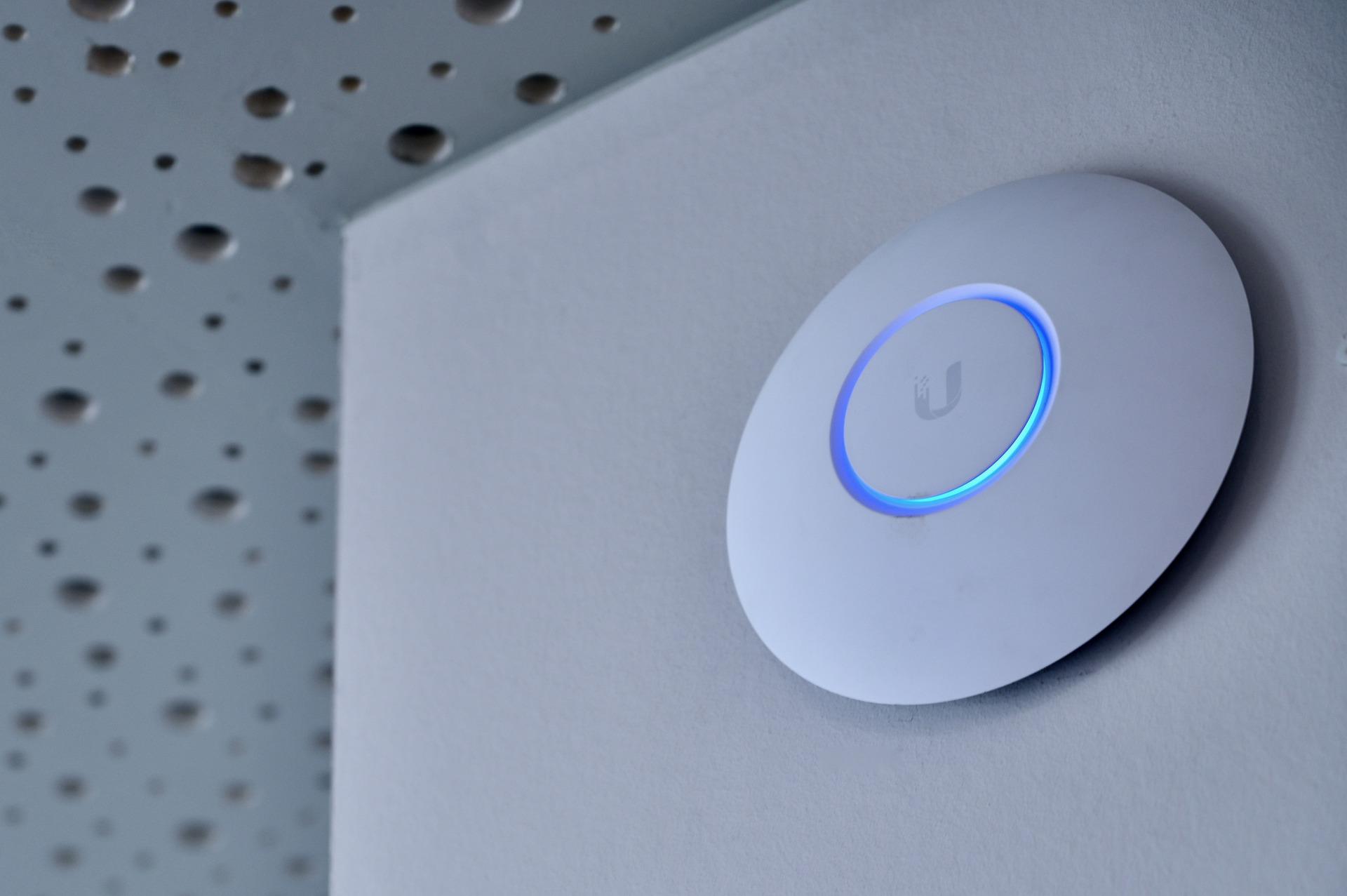 Imagem mostra um access point instalado em uma parede.