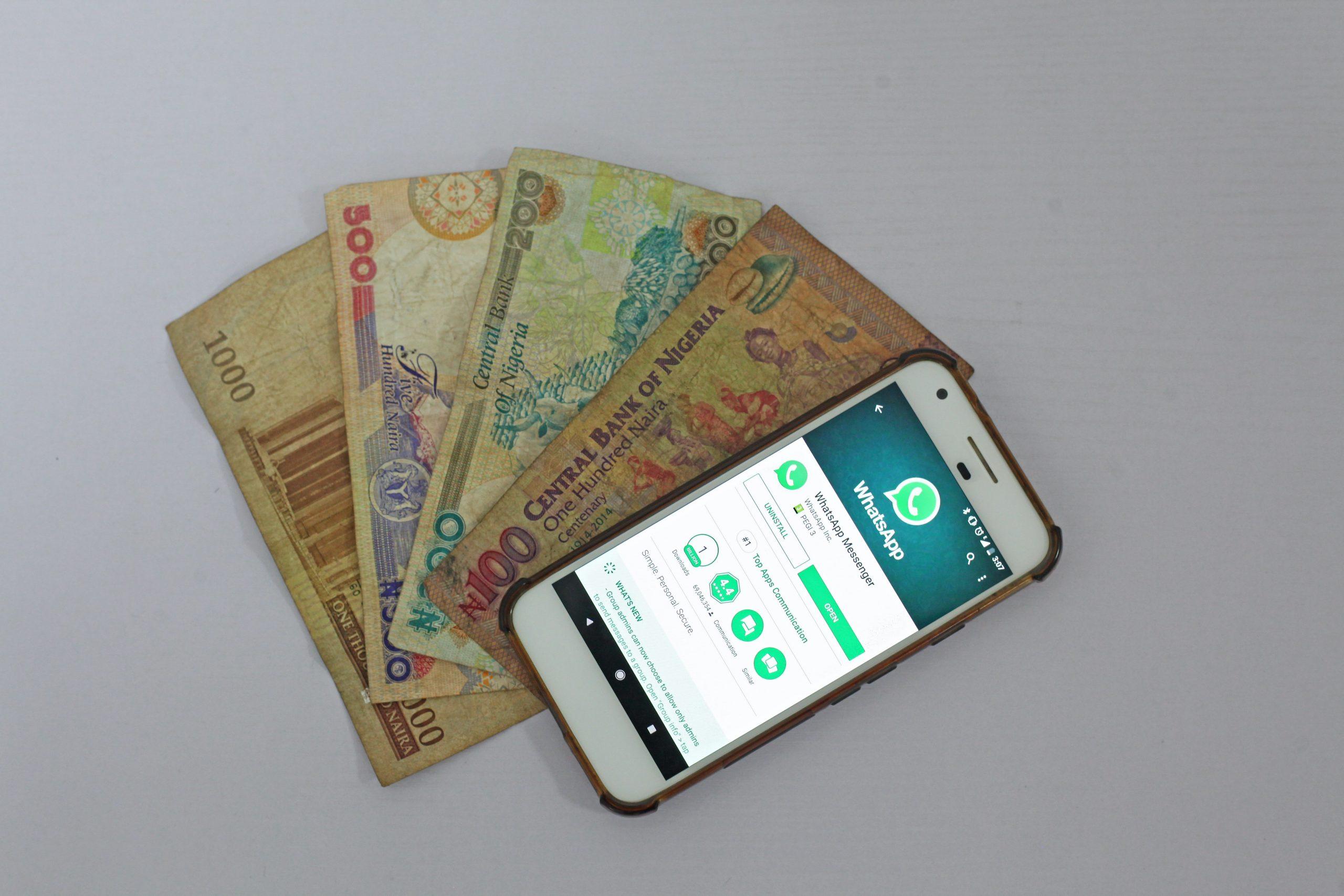 Imagem mostra um celular exibindo a página de download do WhatsApp junto com notas de dinheiro.