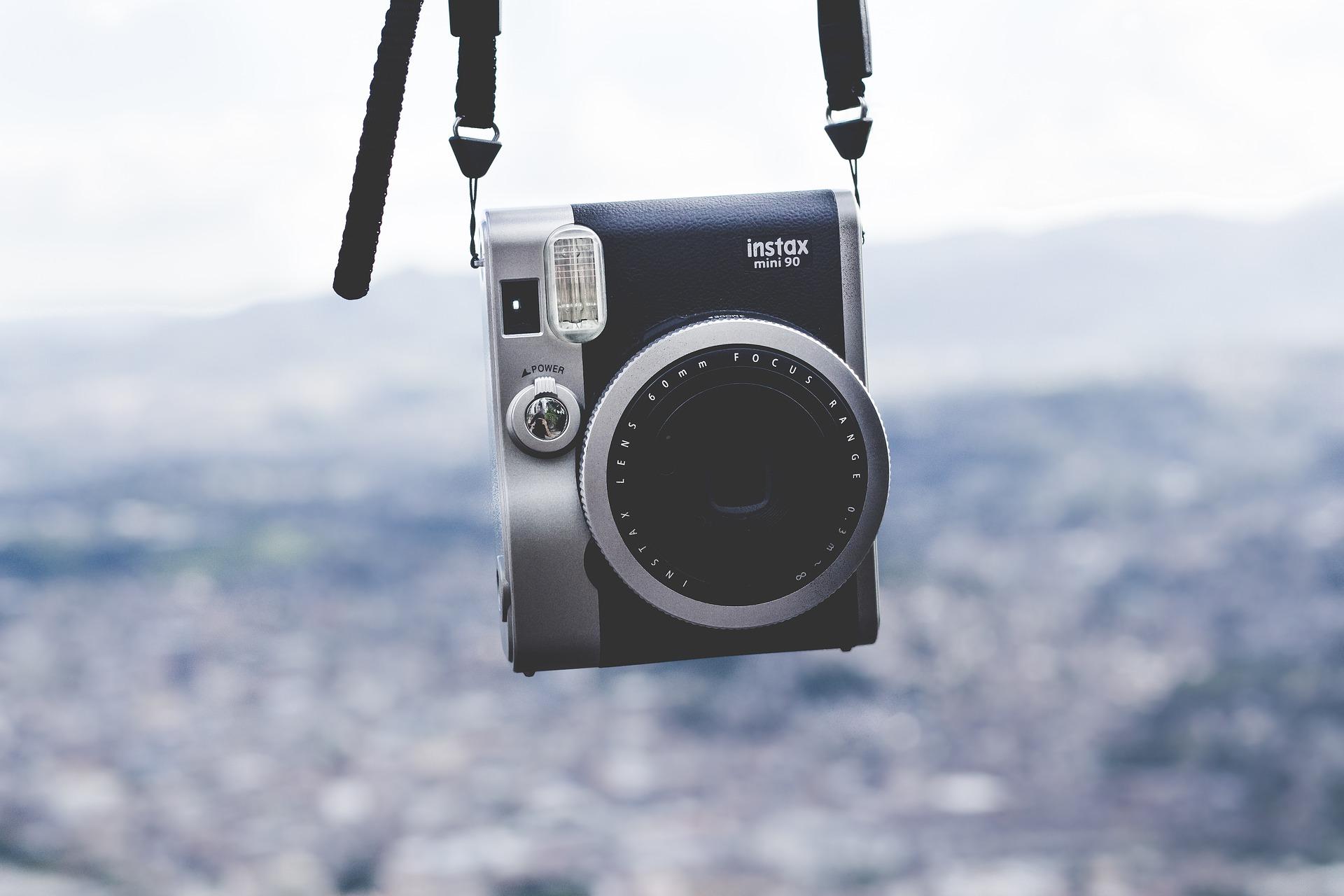 Imagem mostra uma câmera instantânea pendurada.