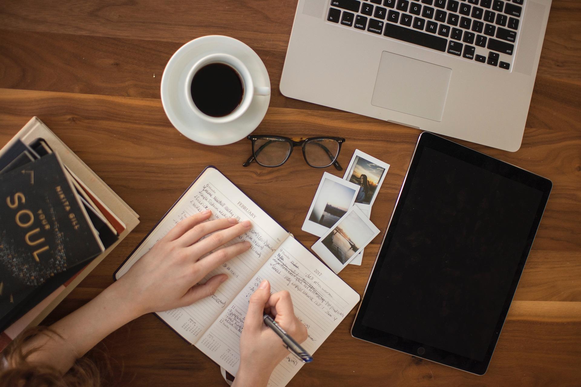 Imagem mostra uma pessoa escrevendo em um caderno com fotos instantâneas ao lado.