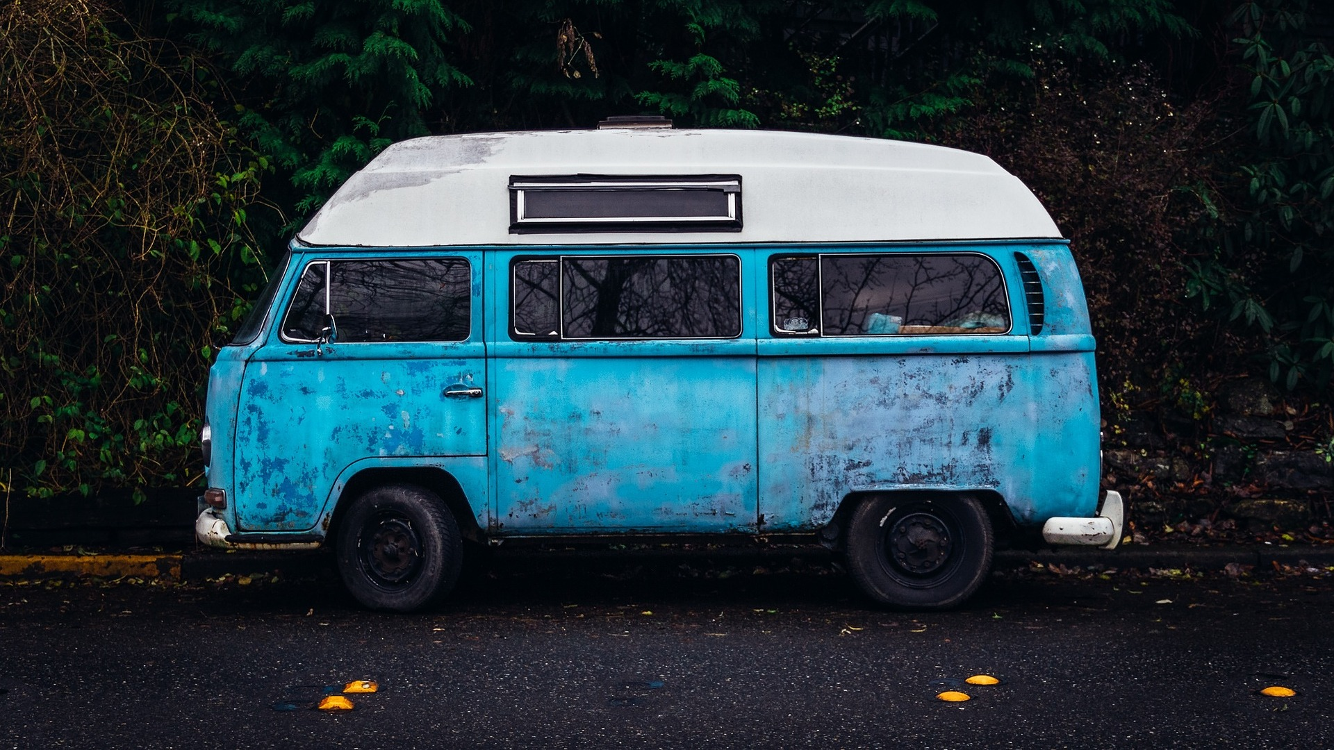 Imagem mostra uma van azul na estrada.