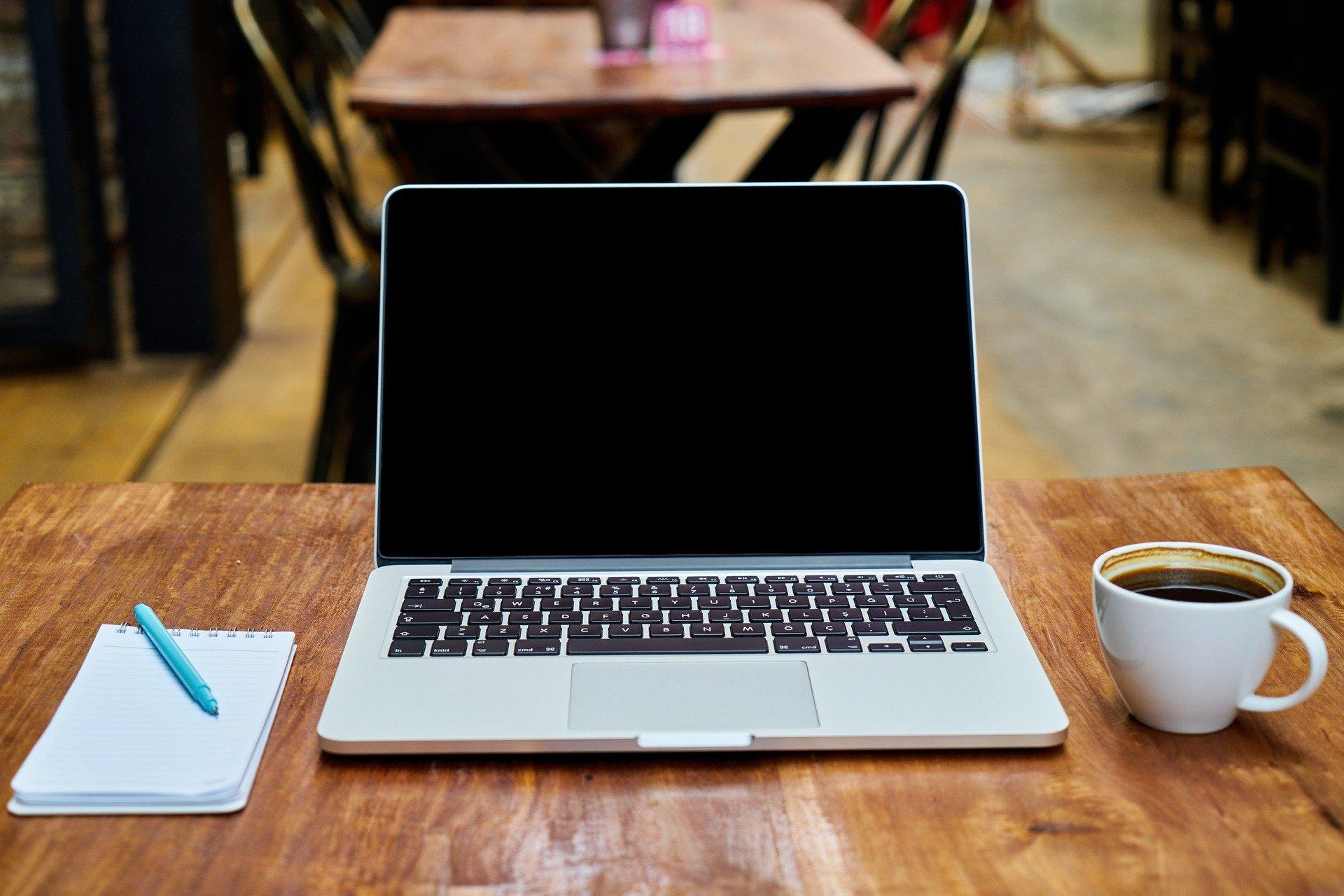 Imagem mostra um notebook sobre uma mesa.