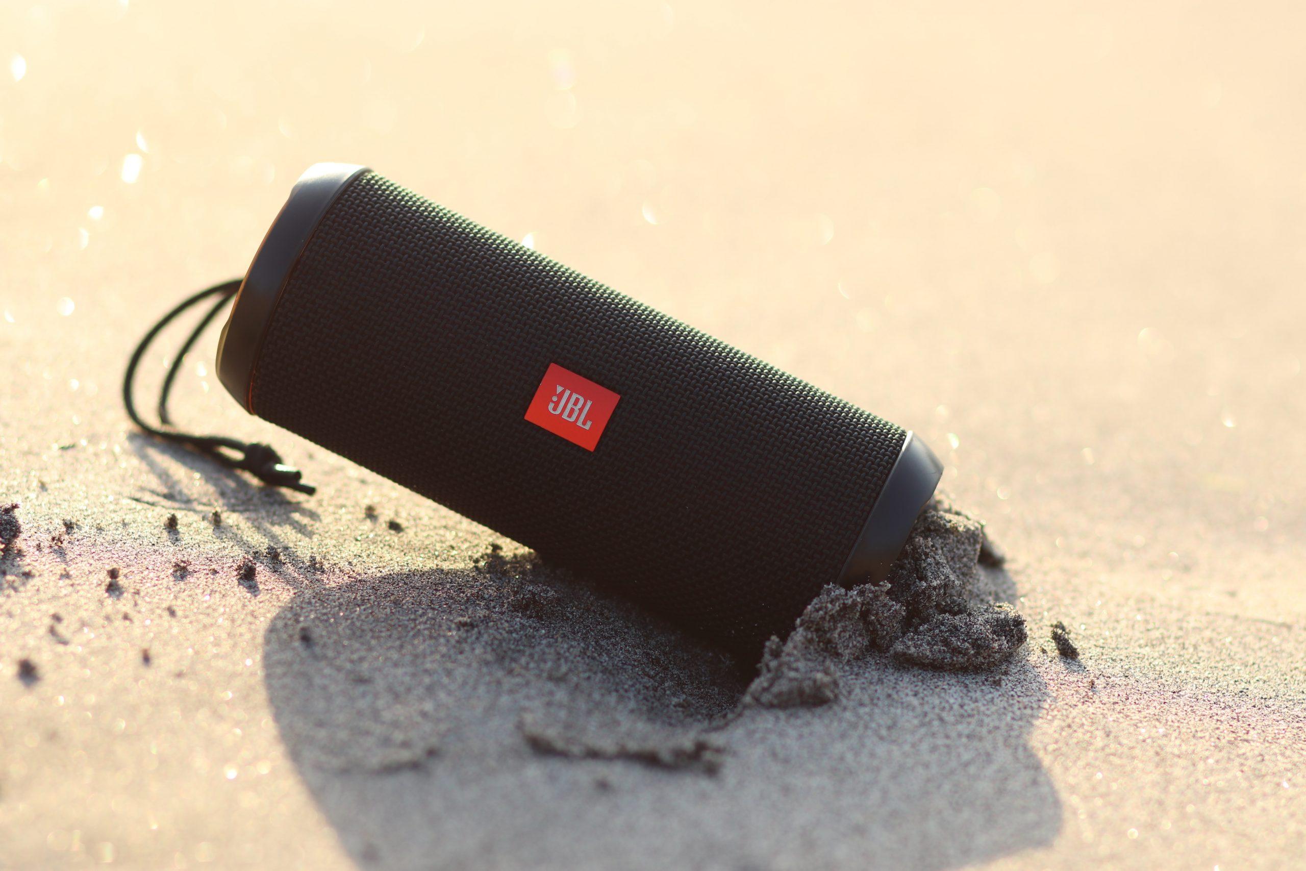 Imagem mostra uma caixa JBL semi-enterrada na areia.
