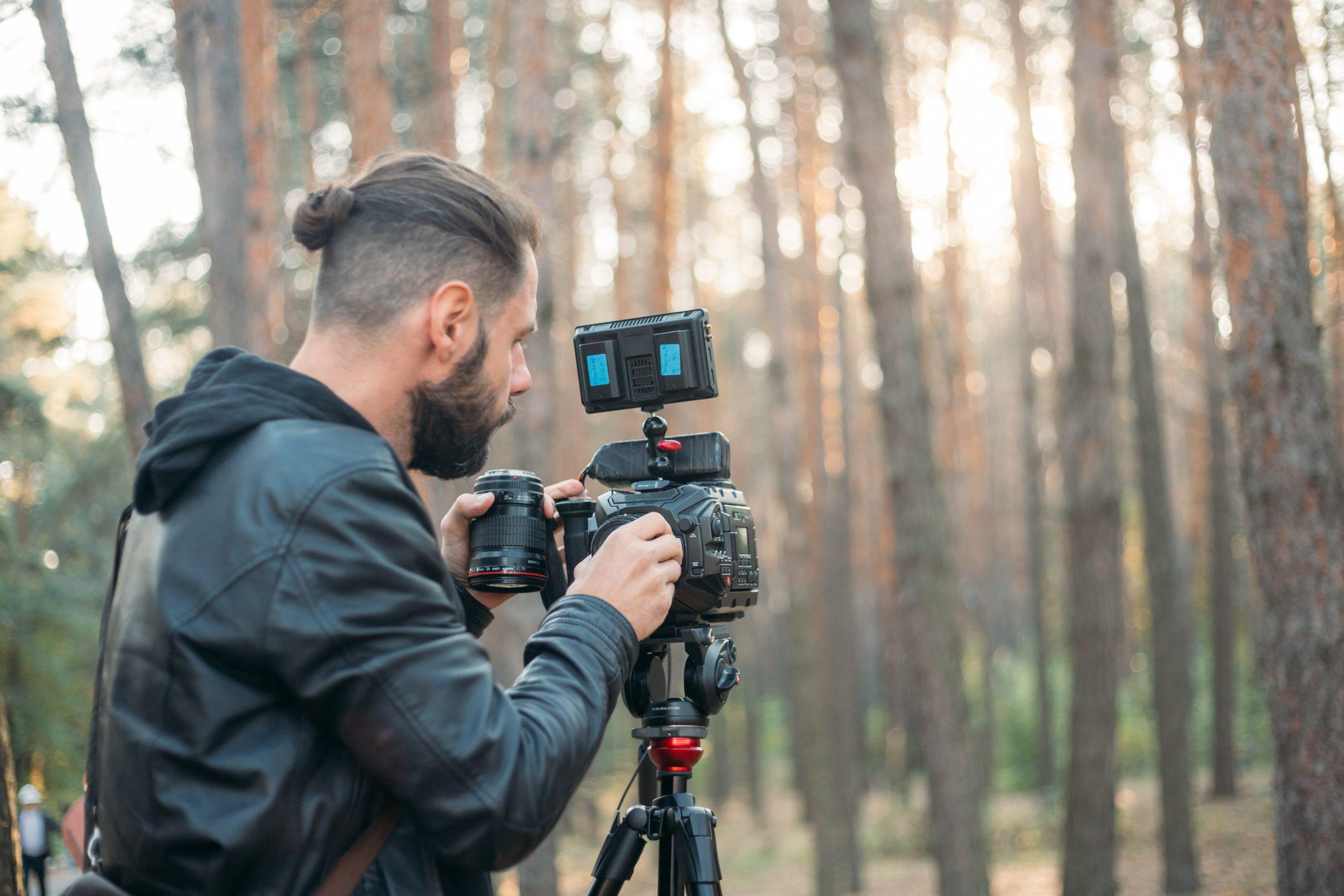 homem ajustando a câmera em um tripé no meio de um cenário de floresta