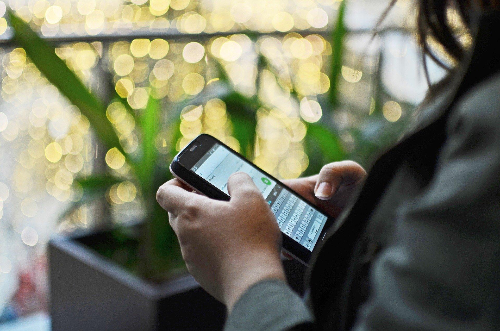 Imagem mostra uma pessoa usando um smartphone.