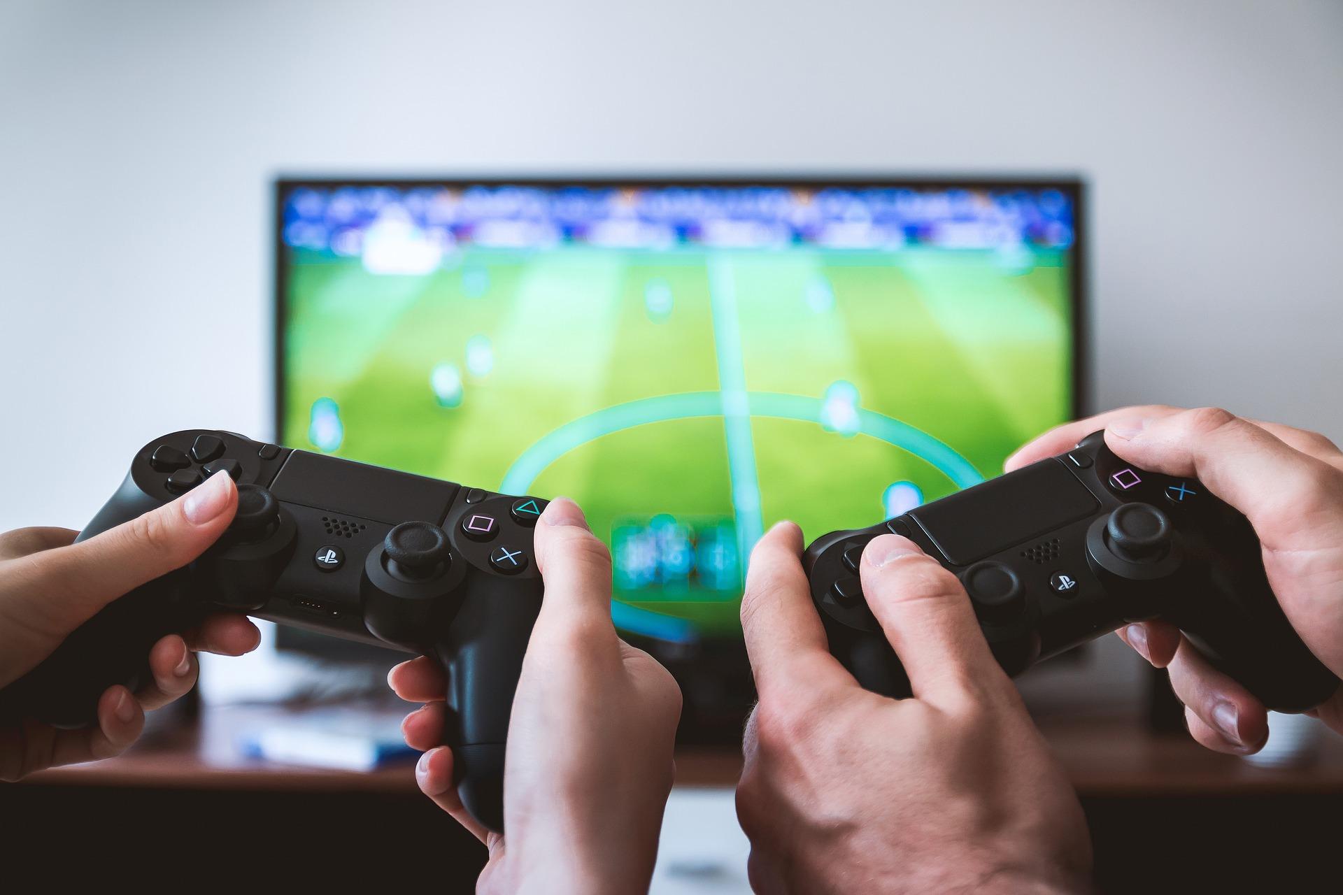 Imagem mostra duas pessoas jogando videogame com gamepads.