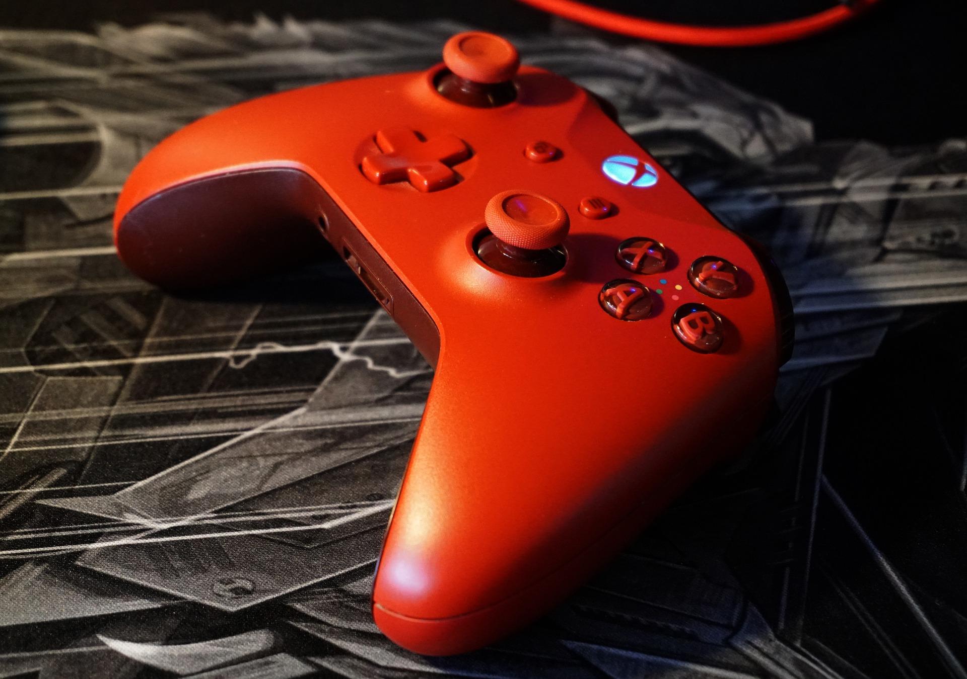 Imagem mostra um gamepad vermelho em destaque.