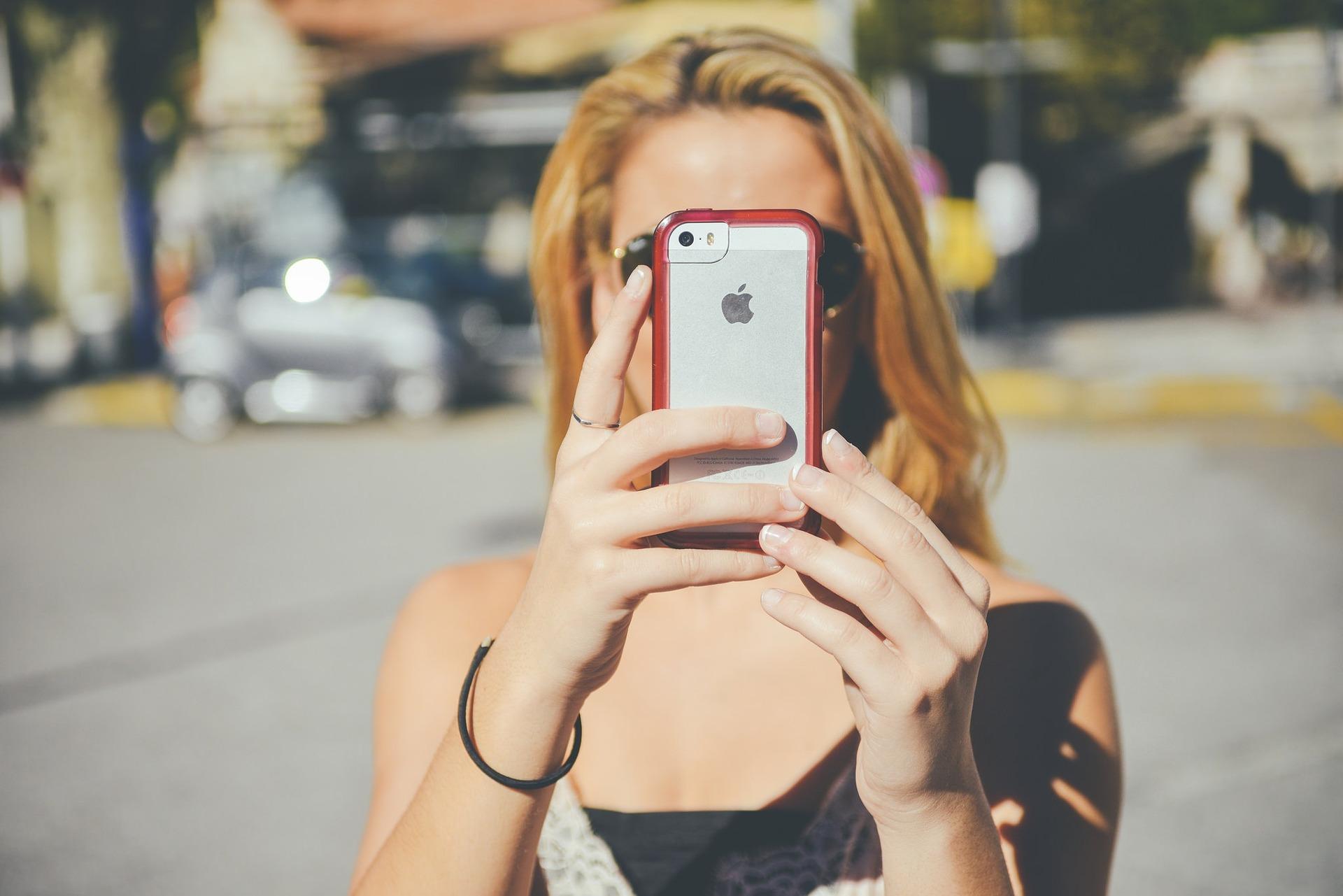 Imagem mostra uma mulher segurando um Iphone em frente o rosto.