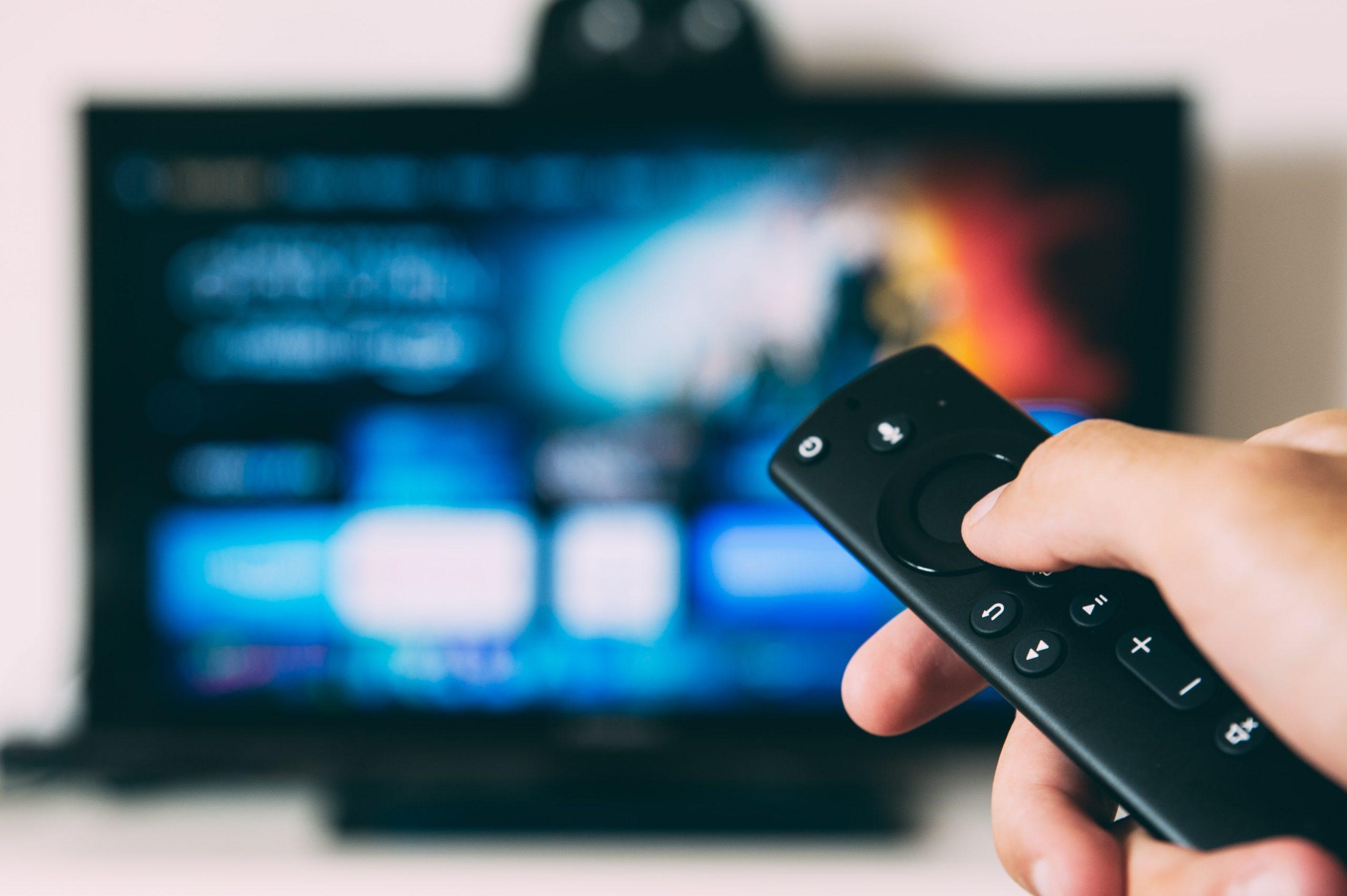 uma pessoa segurando um controle remoto preto na mão e apontando para uma televisão