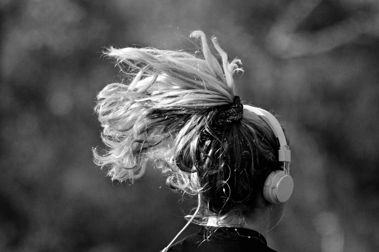 Imagem mostra uma mulher com fone de ouvido e cabelos esvoaçantes.