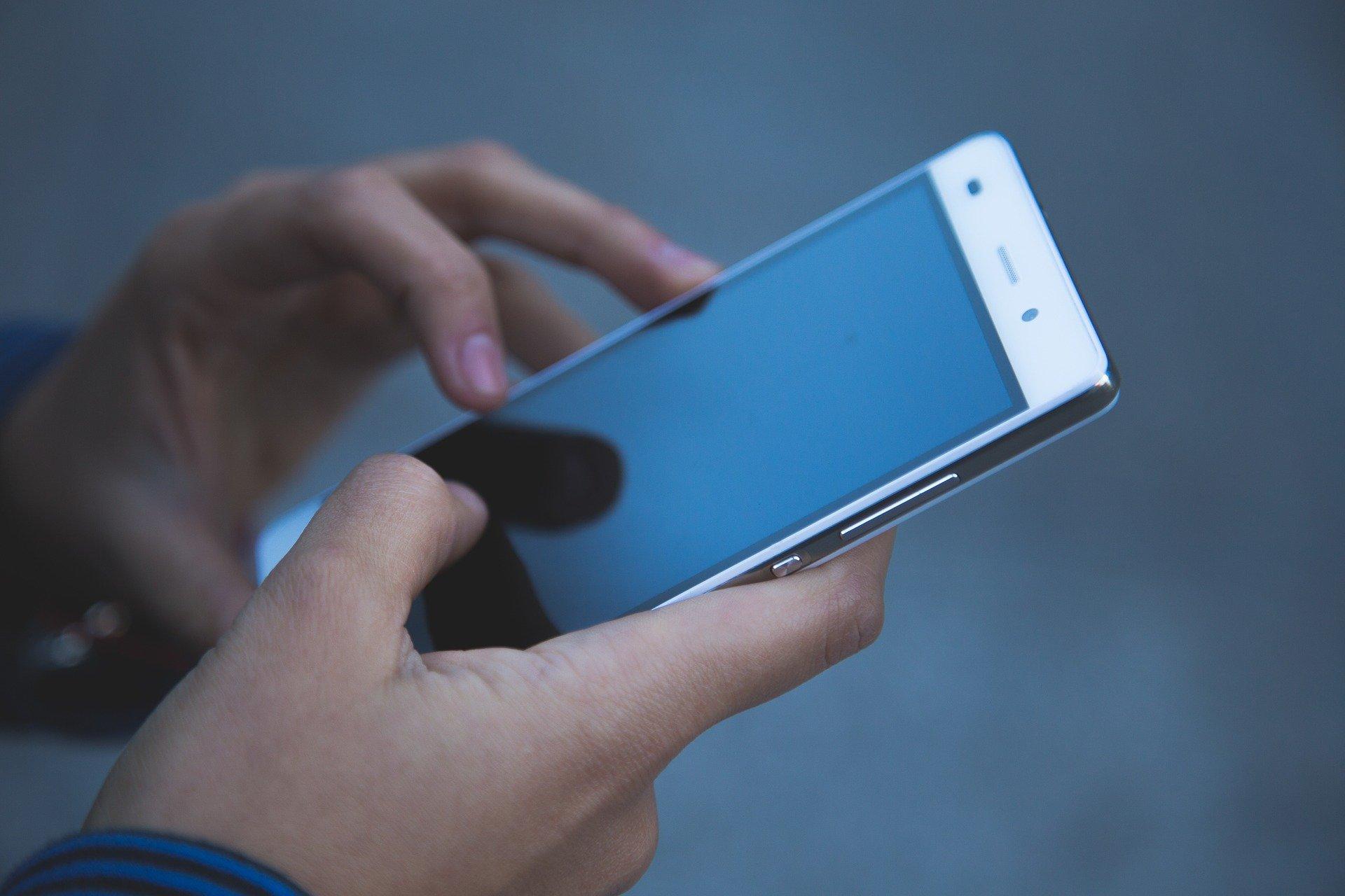 Imagem mostra uma pessoa segurando um celular.