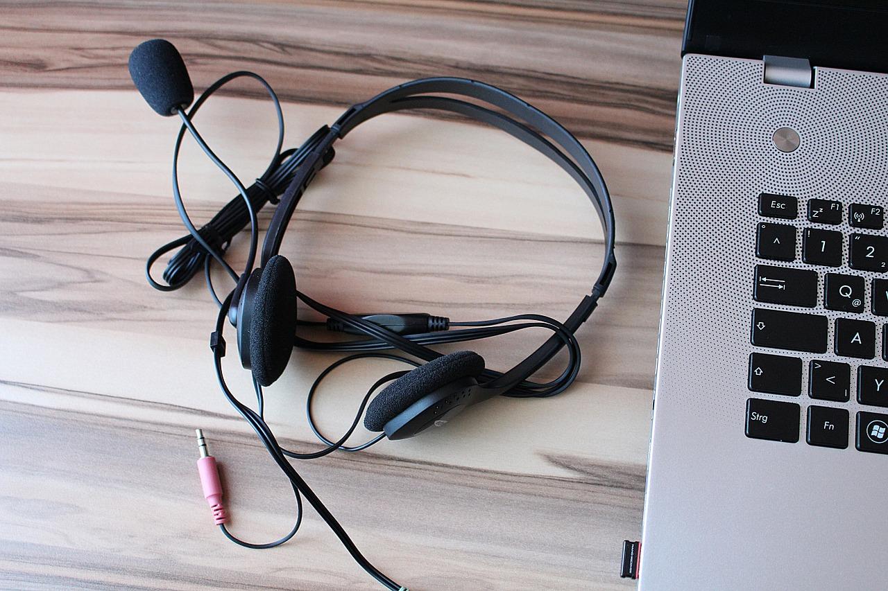 Imagem mostra um headphone com fio ligado a um notebook.