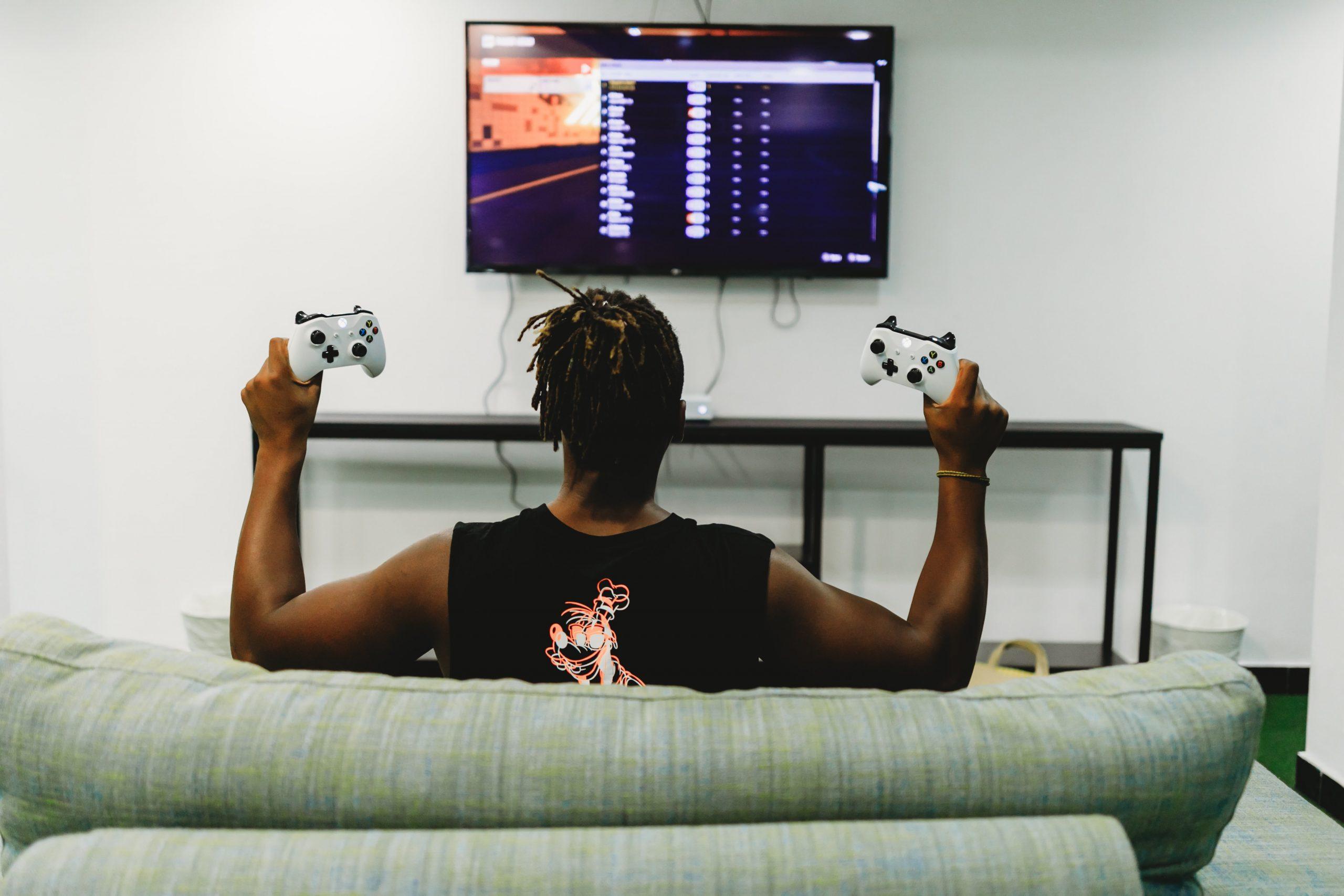 Homem sentado no sofá, de frente para a TV e segurando dois controles de Xbox.