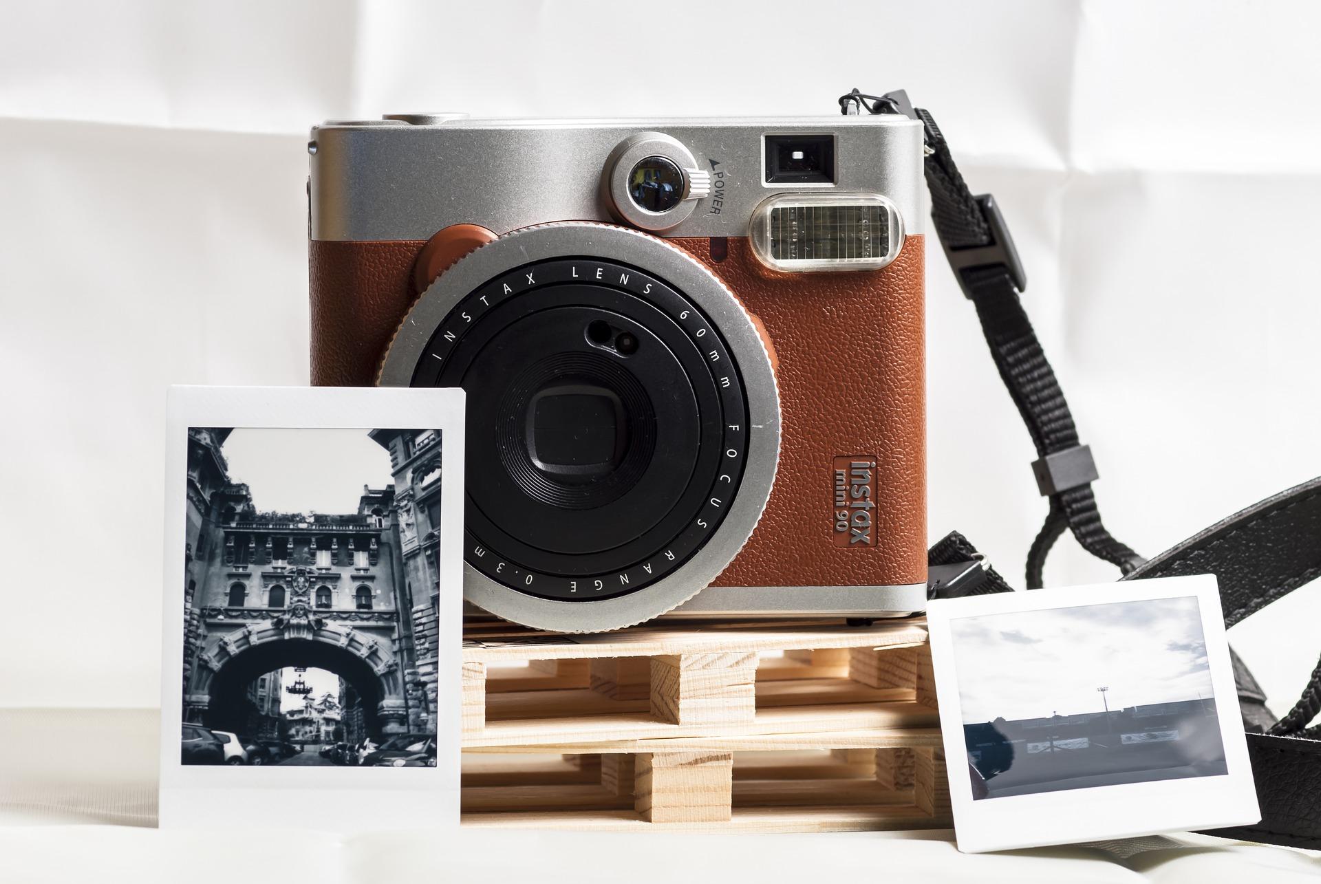 Imagem mostra uma câmera instantânea ao lado de fotografias turísticas.