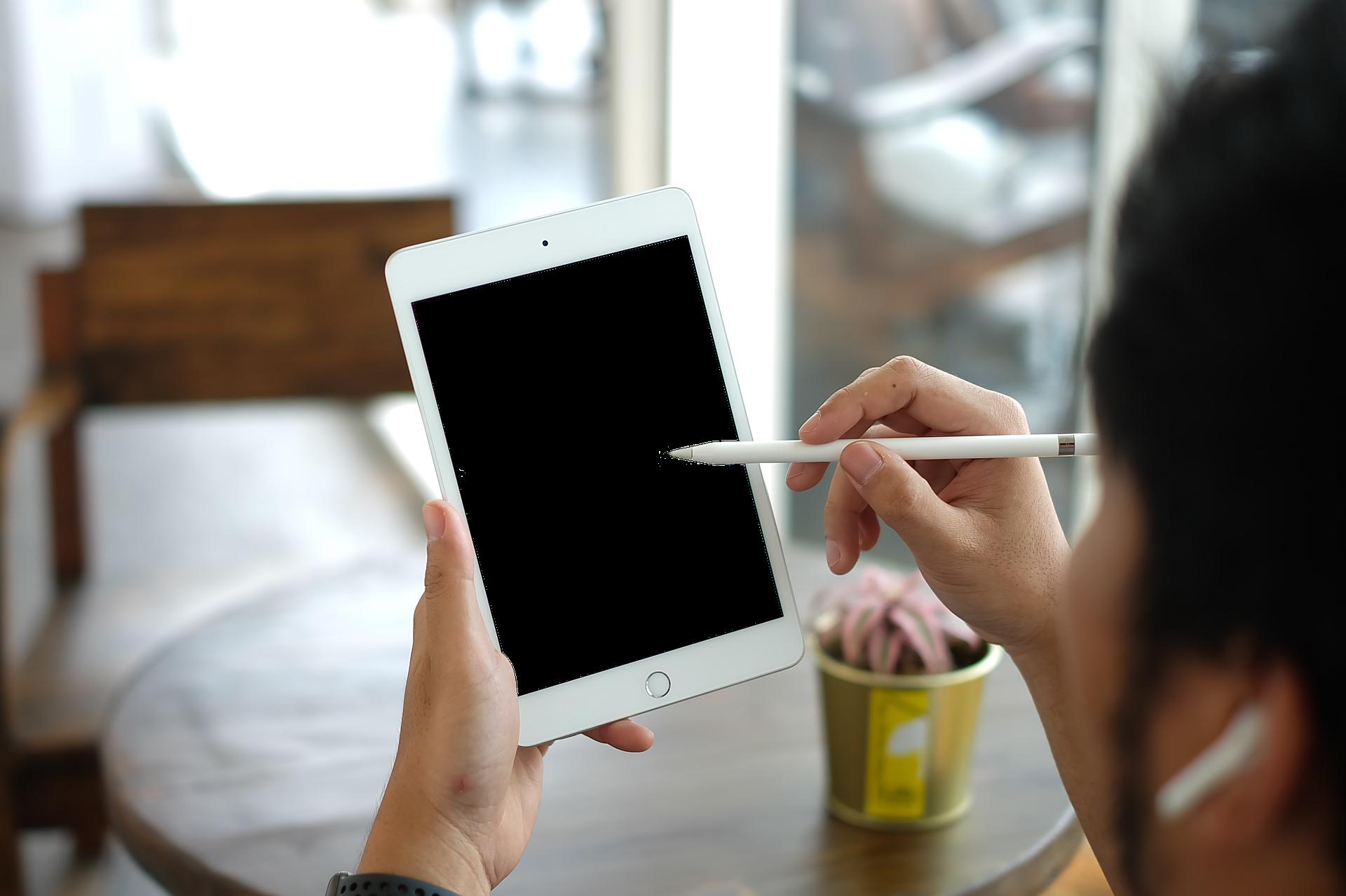 Imagem mostra uma pessoa usando uma caneta em um tablet.