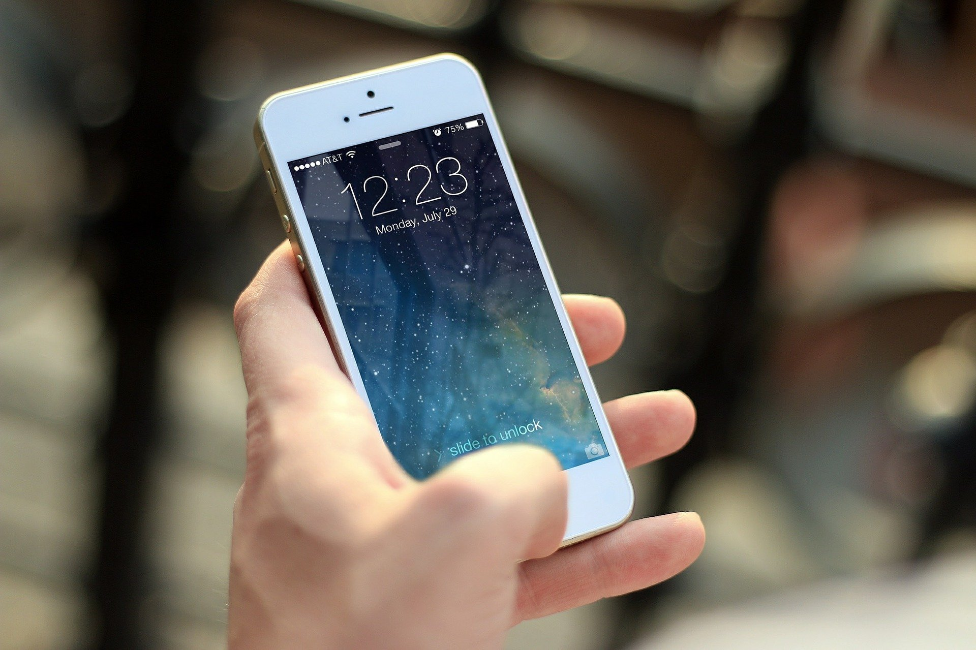 Imagem mostra uma pessoa segurando um smartphone na tela inicial.