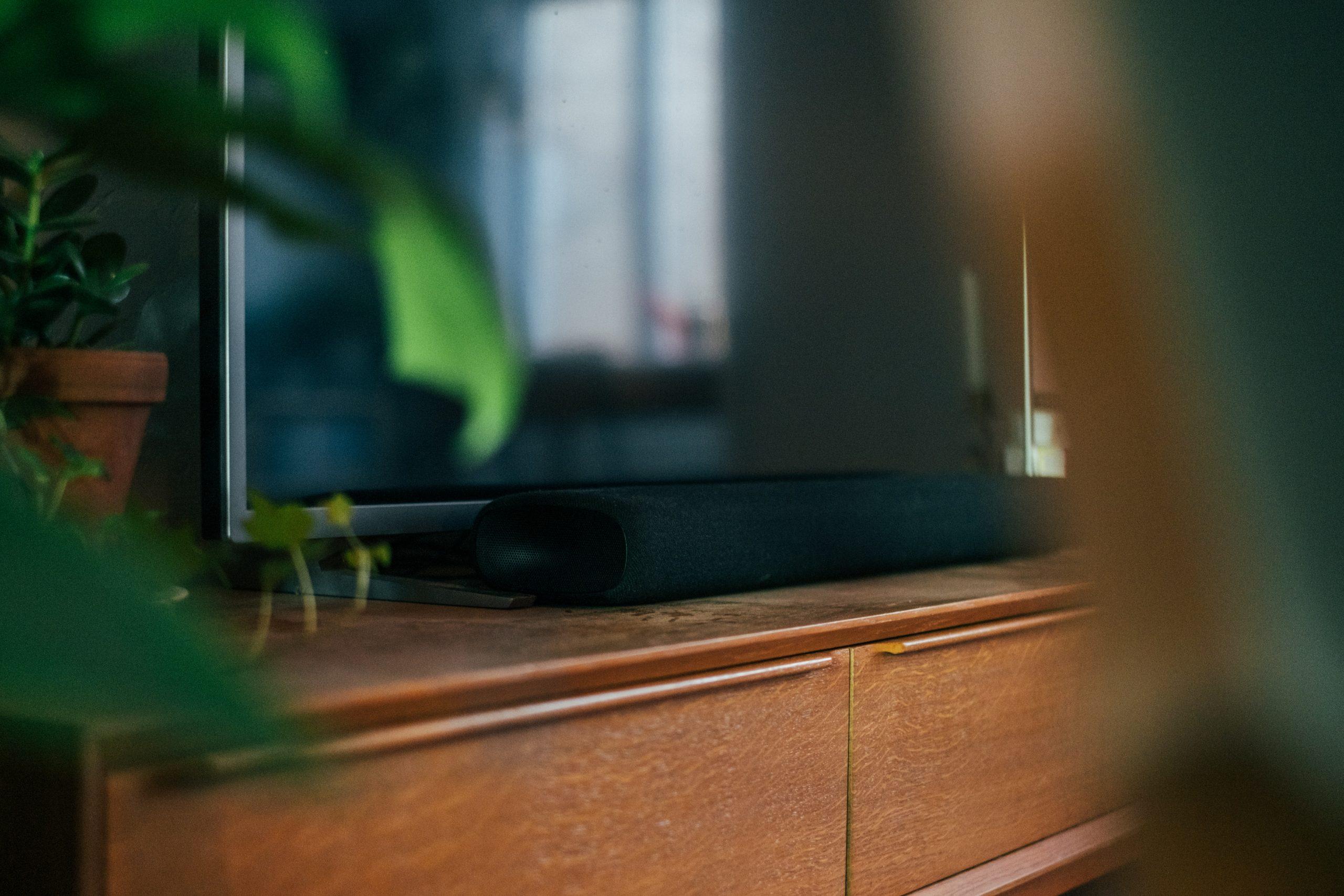 Imagem mostra uma TV com soundbar sobre um móvel.