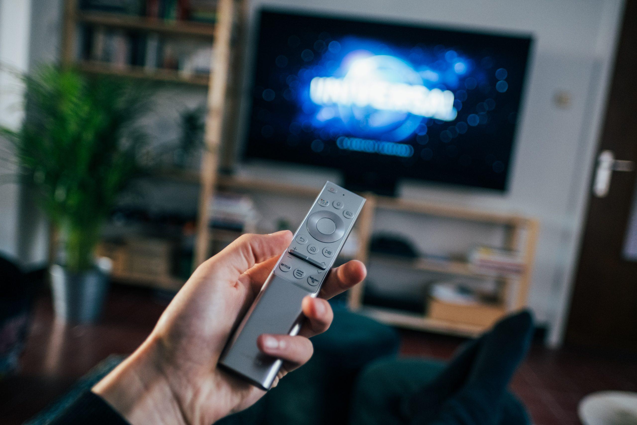 controle remoto apontado para uma televisão