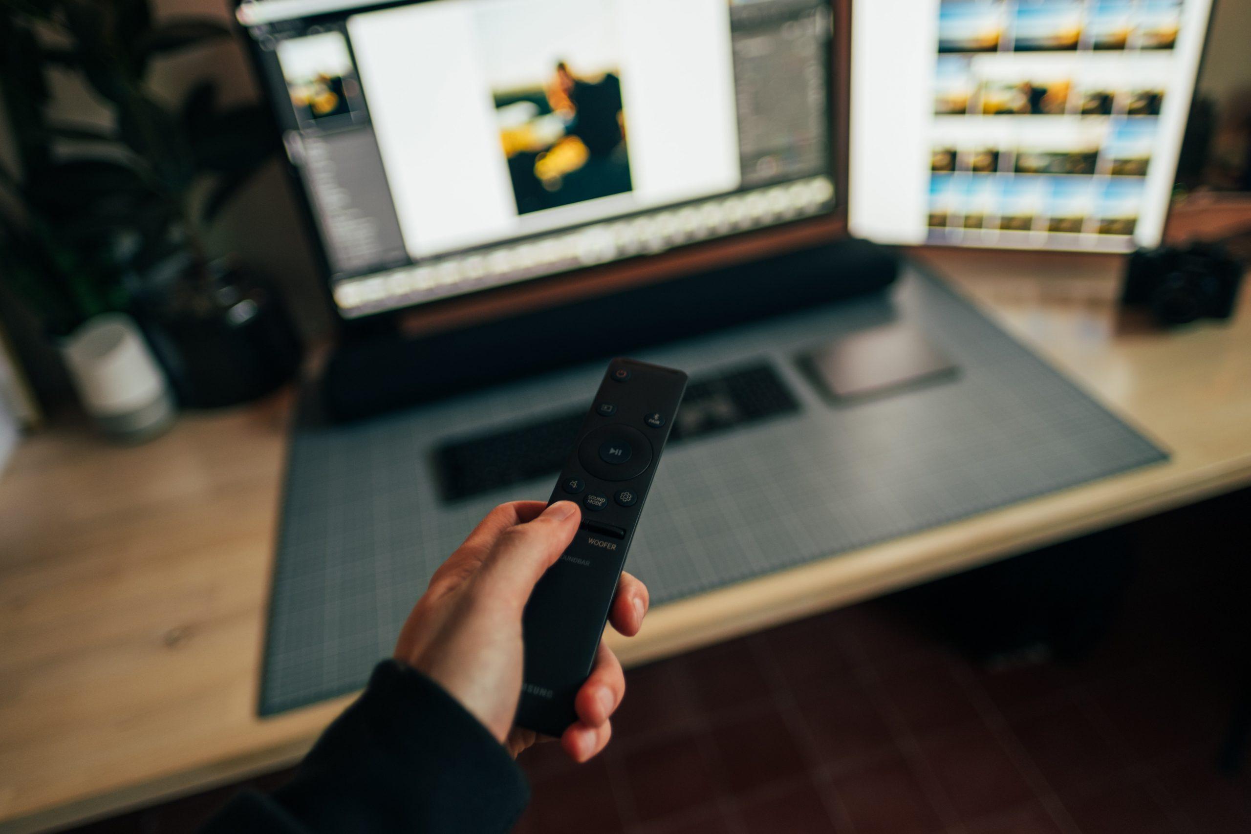 Imagem mostra uma pessoa usando um controle remoto em frente a um monitor e uma soundbar.