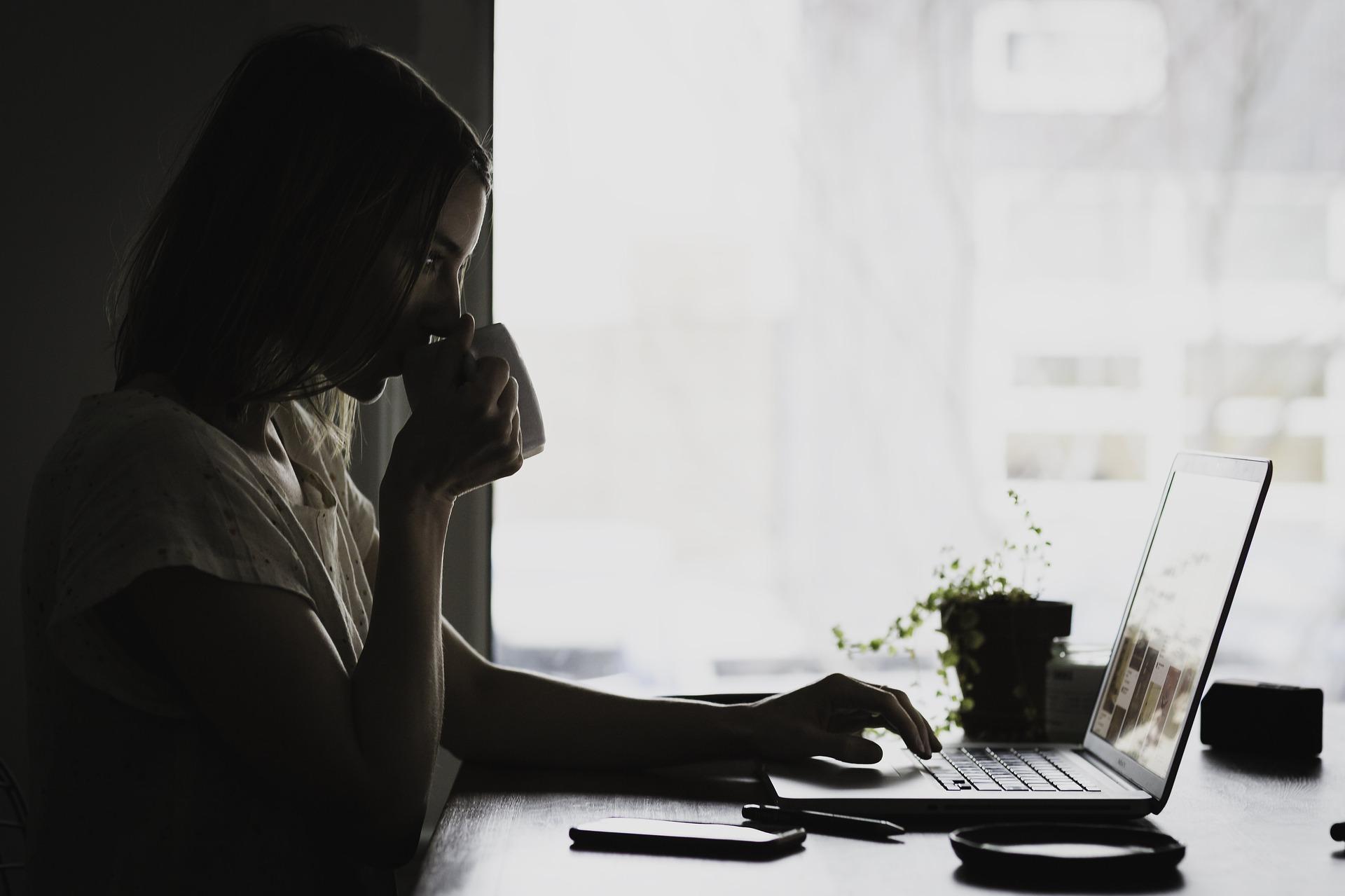Imagem mostra uma mulher olhando para um notebook enquanto bebe café.
