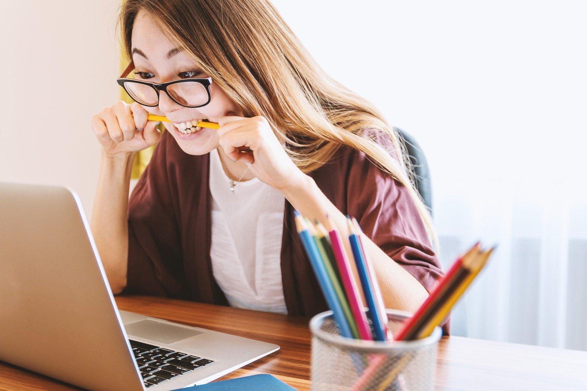 Imagem mostra uma mulher com um lápis na boca olhando para um notebook.