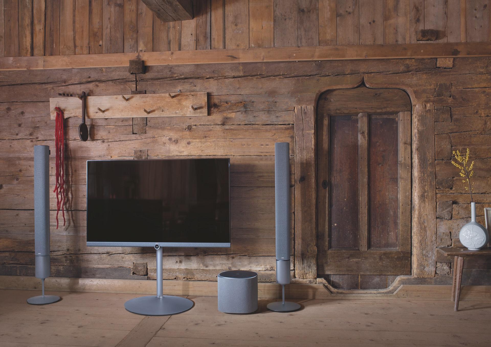 Imagem mostra uma sala de estar com várias caixas de som espalhadas.