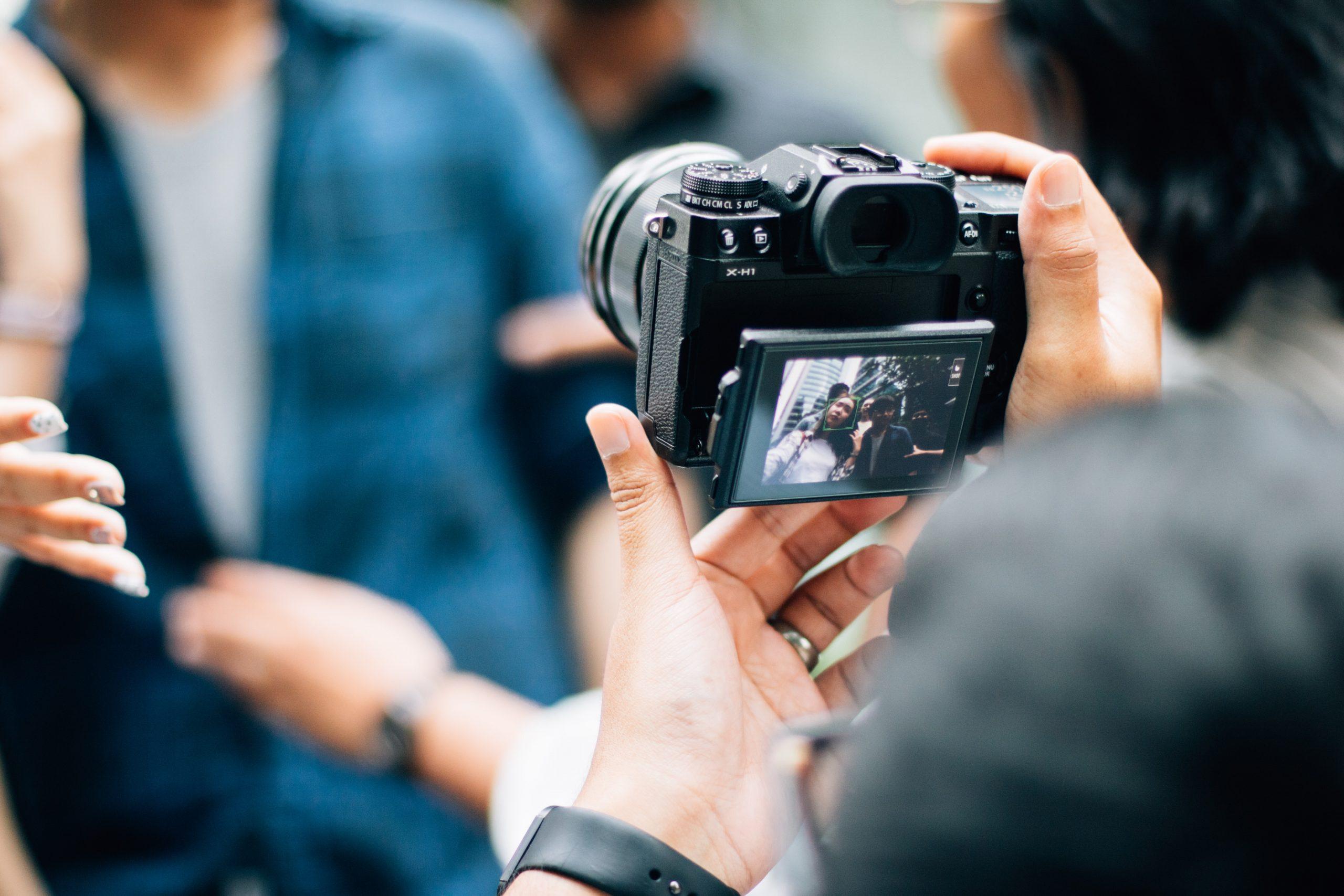 Imagem mostra uma pessoa segurando uma câmera com o visor aberto.