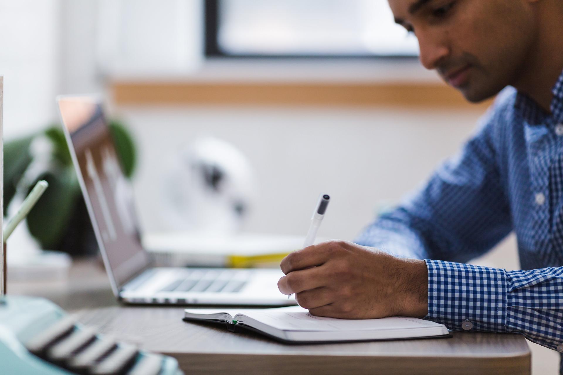 Imagem mostra um homem fazendo anotações em uma caderneta ao lado de um notebook.