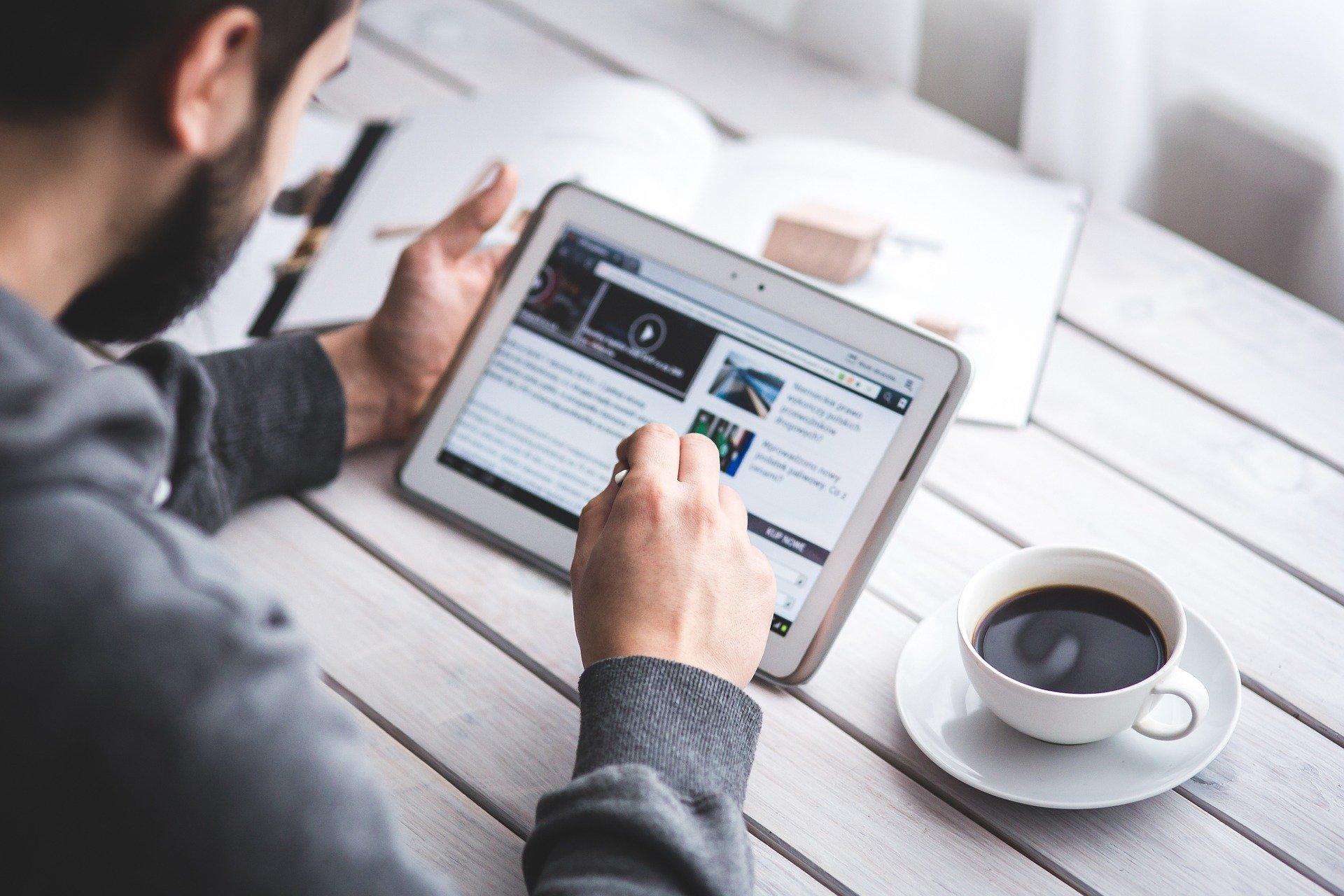 Imagem mostra um homem observando gráficos em um tablet.
