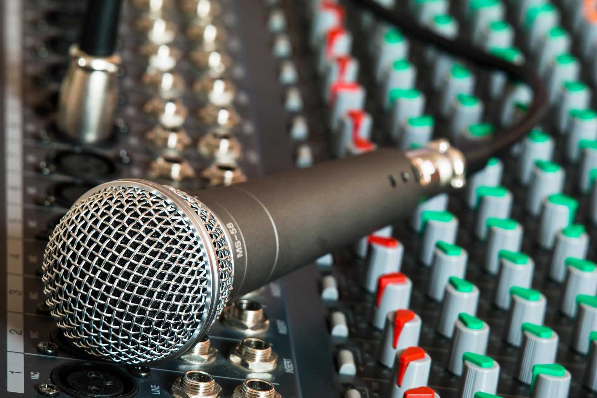 Imagem mostra um microfone conectado por cabo a uma mesa de som.