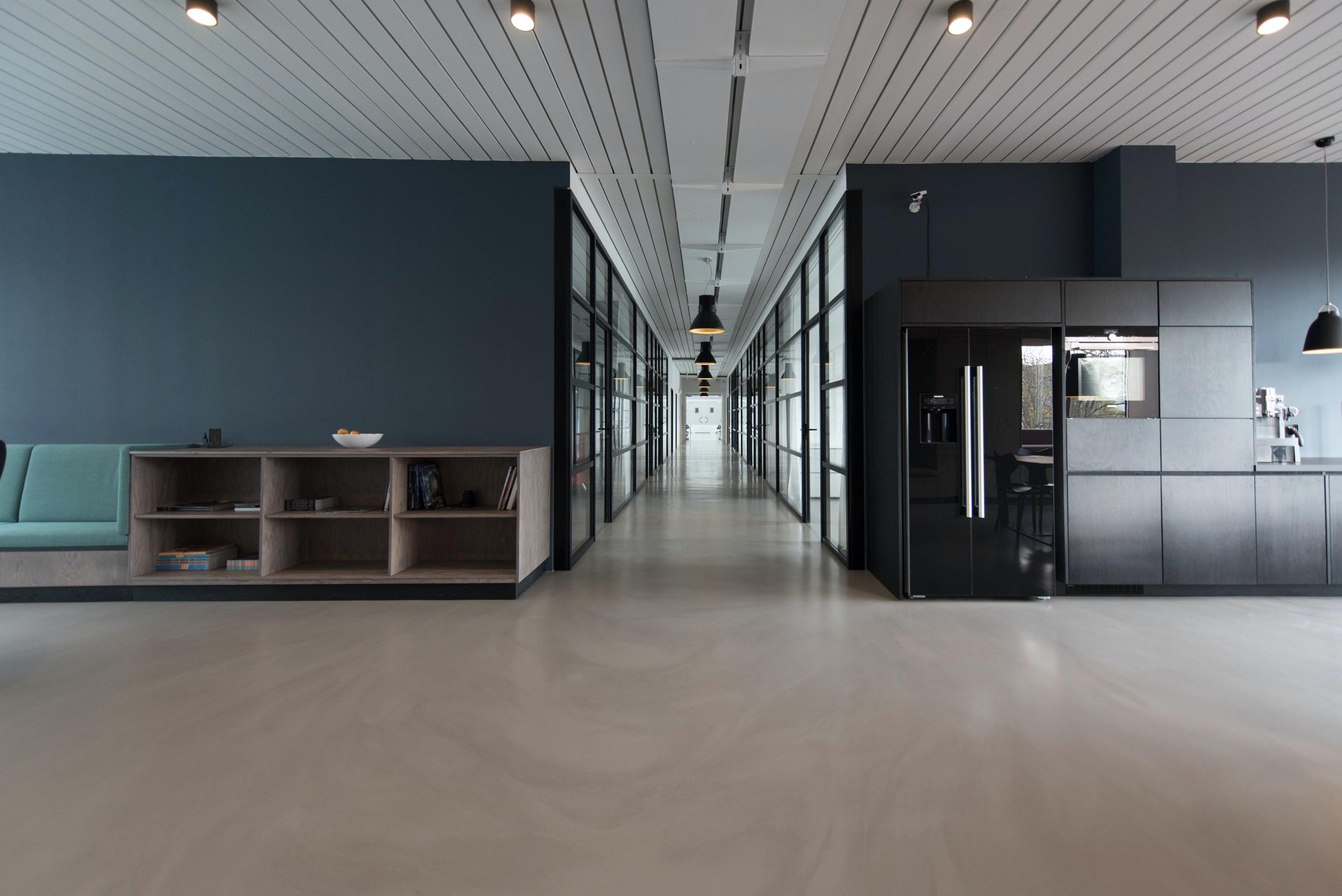 Imagem mostra uma ampla sala com um corredor ao fundo.