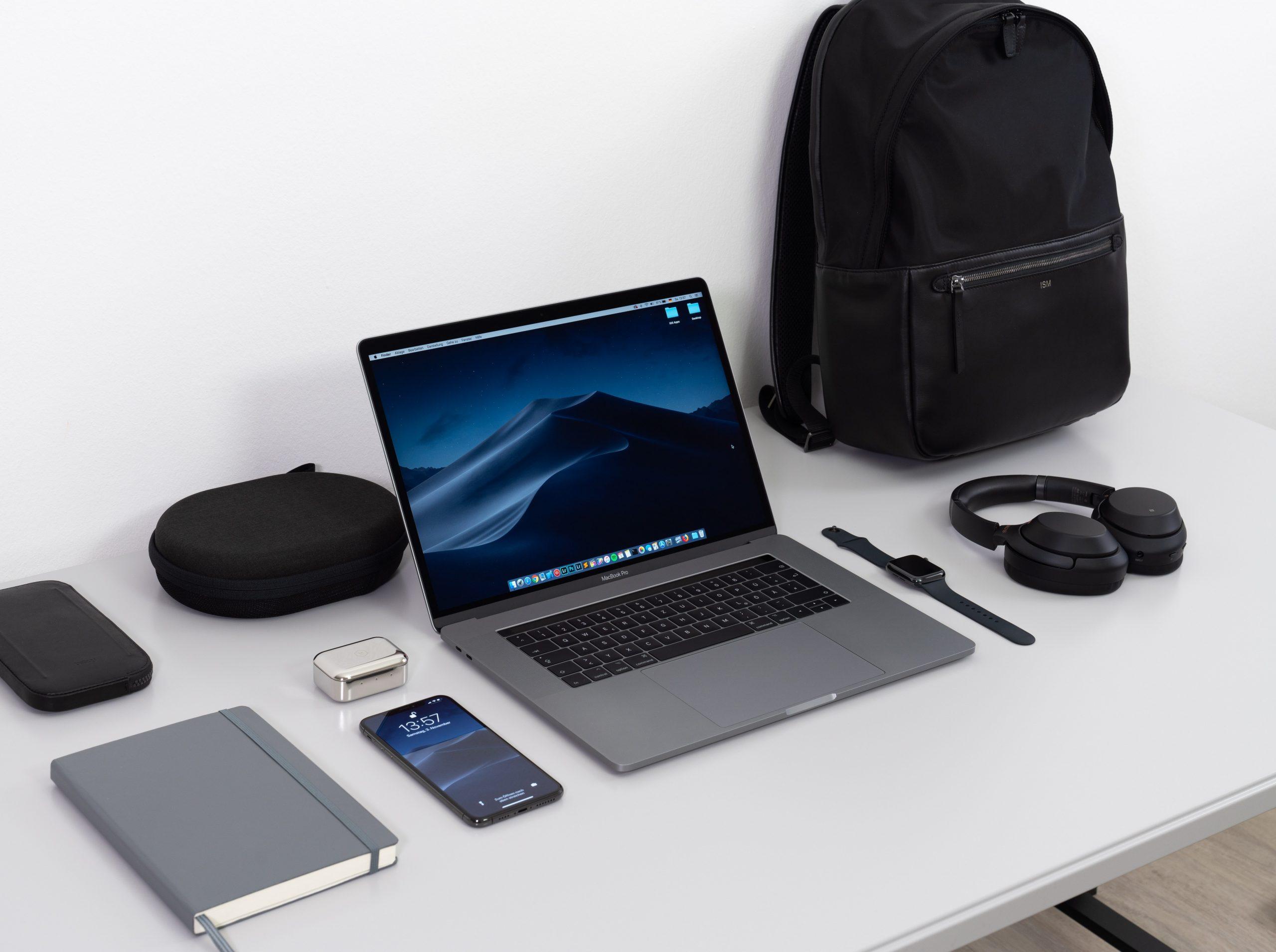 Imagem de uma mochila de computador ao lado de alguns eletrônicos.