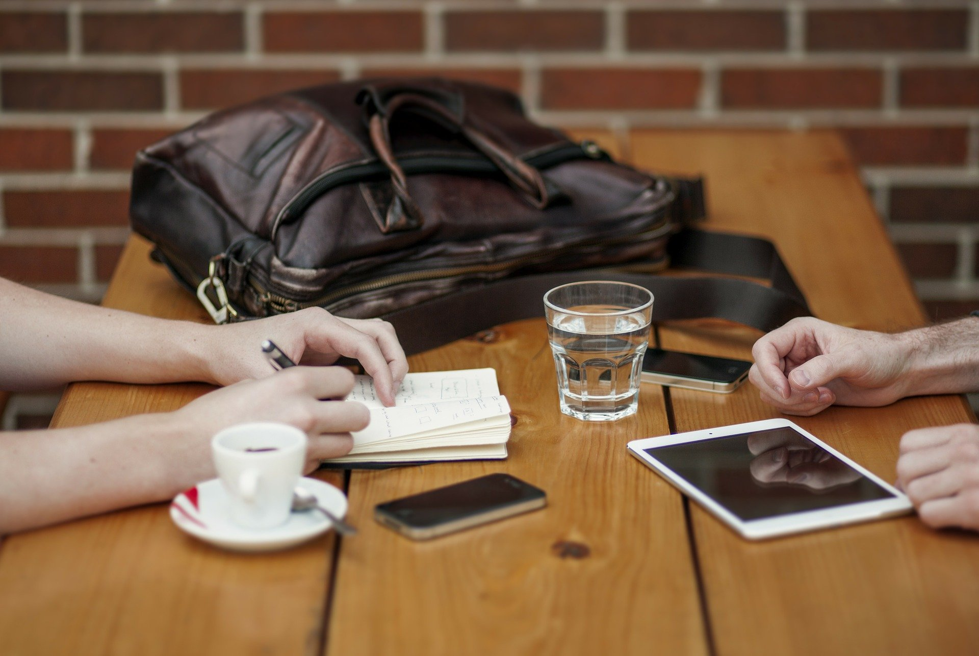 Imagem mostra um tablet, um smartphone e um caderno em destaque sobre uma mesa.