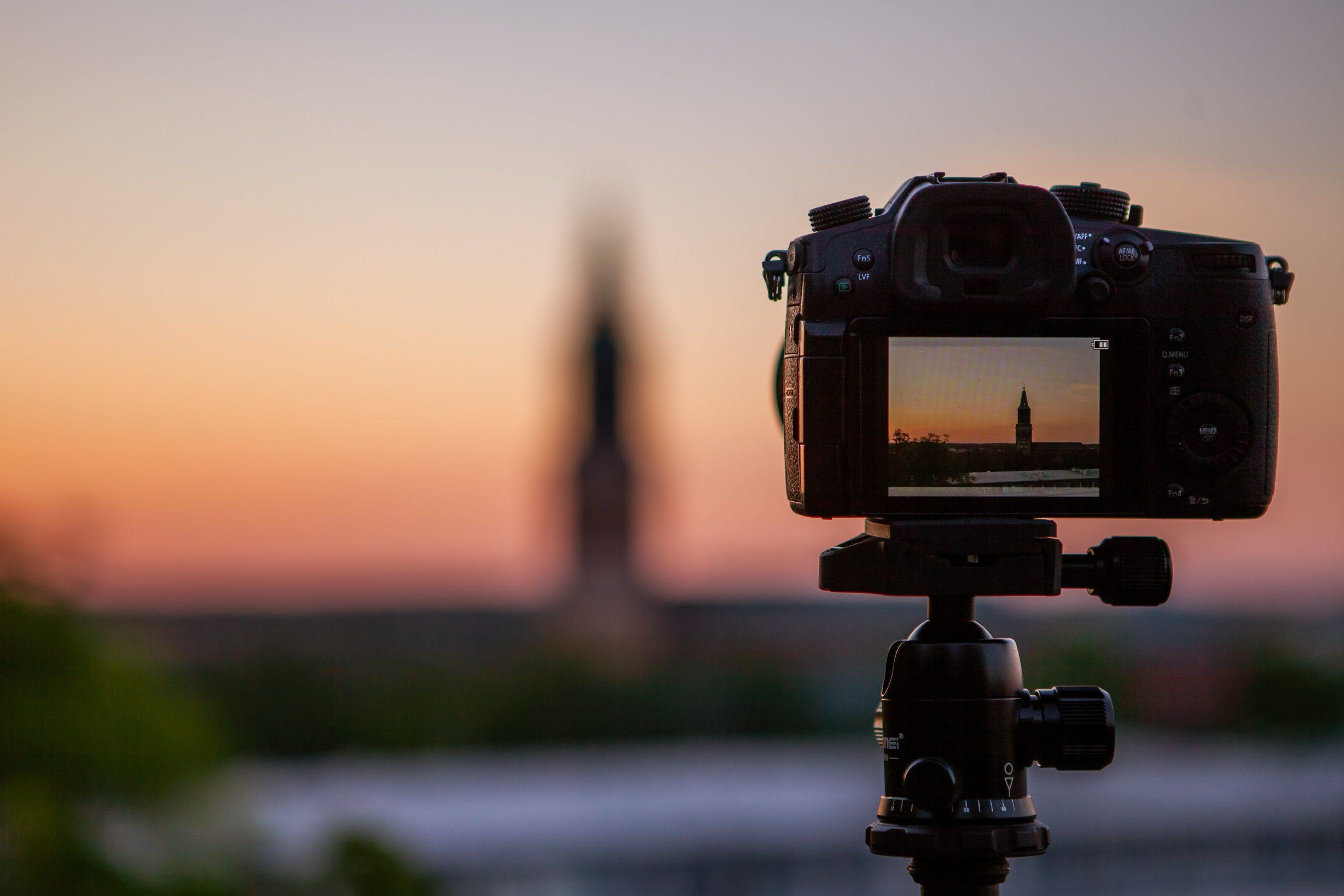 câmera em cima de um tripé capturando o pôr-do-sol