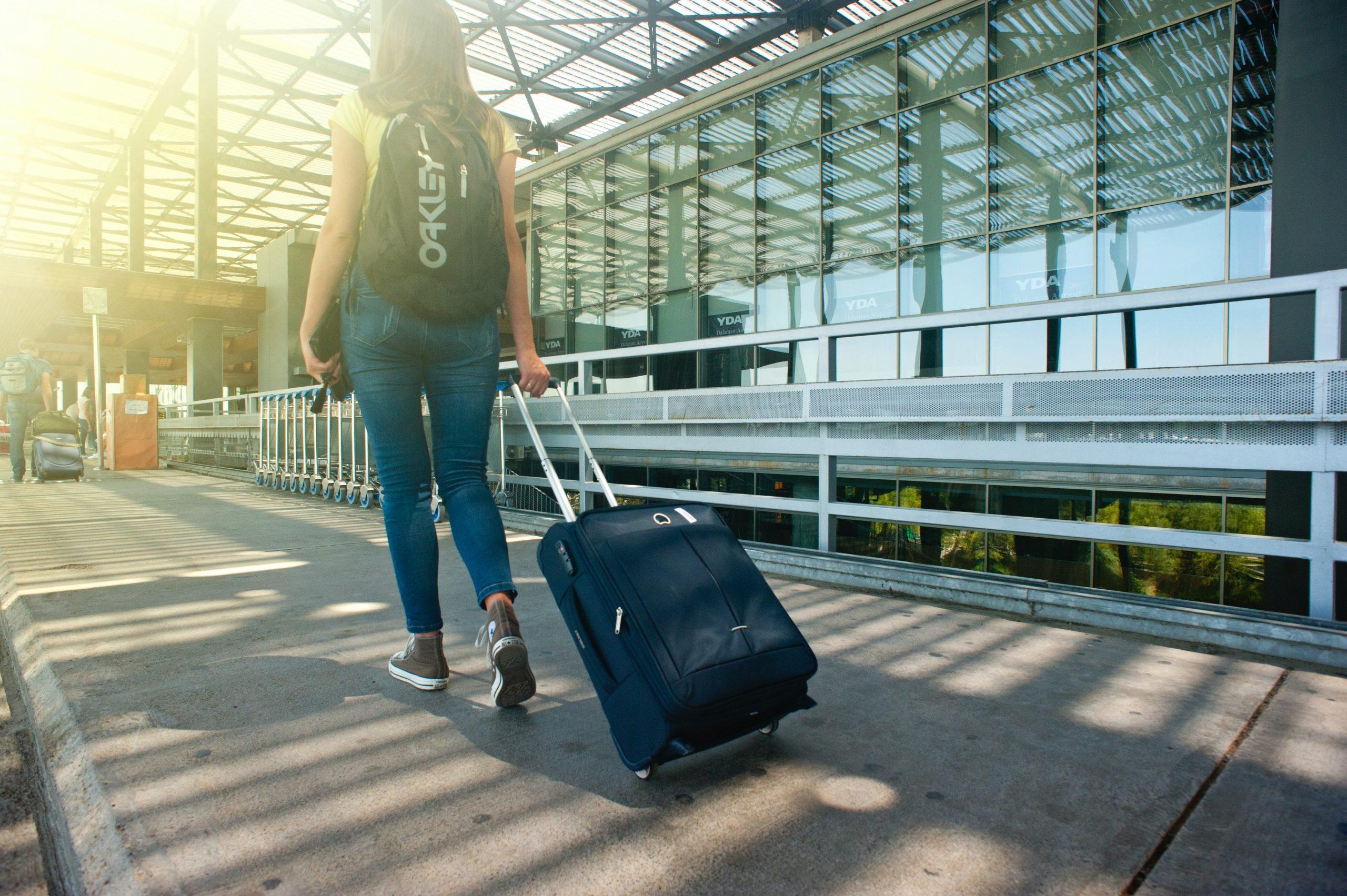 Imagem de uma mulher puxando uma mochila de carrinho.