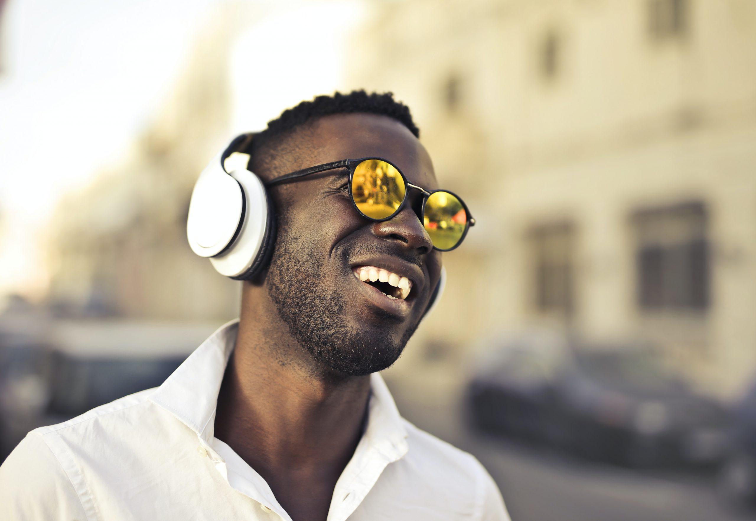 Imagem mostra um homem na rua com fones de ouvido.