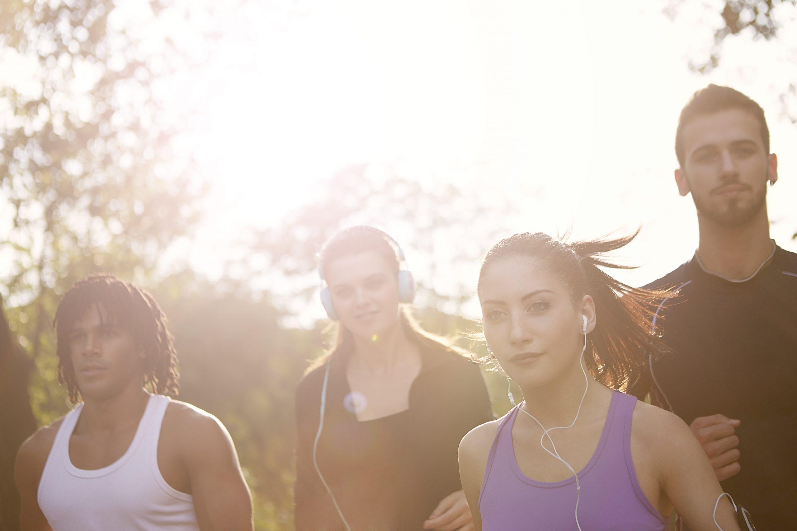 Imagem mostra um grupo de pessoas usando fones e correndo.