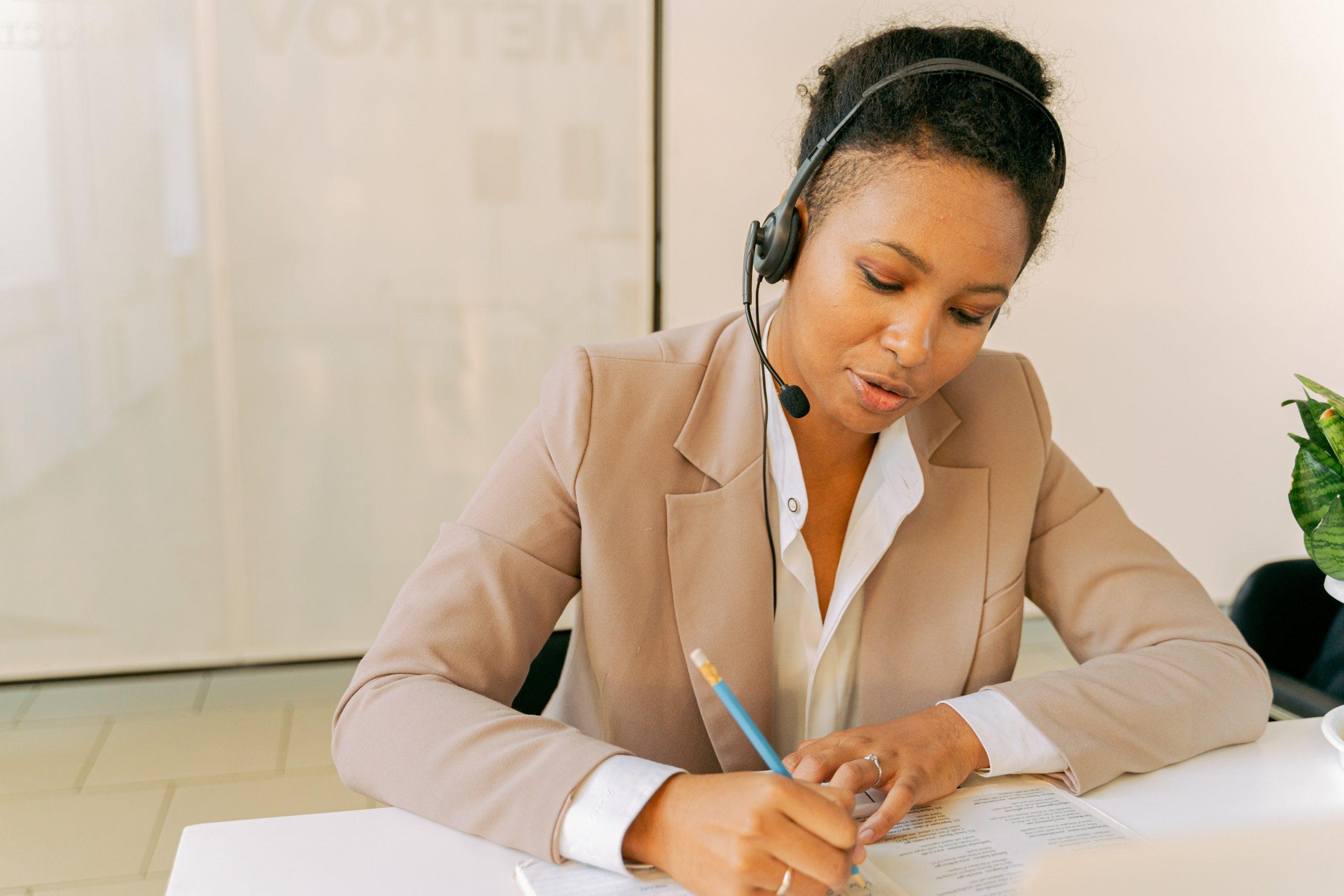 Imagem mostra uma mulher com roupa social usado um headset enquanto faz anotações.
