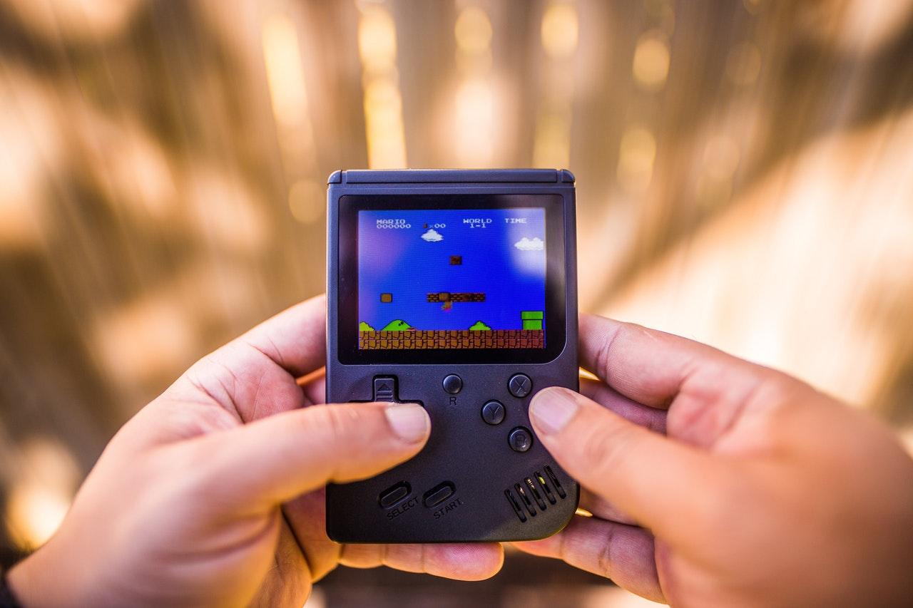 Imagem mostra uma pessoa jogando Game Boy.