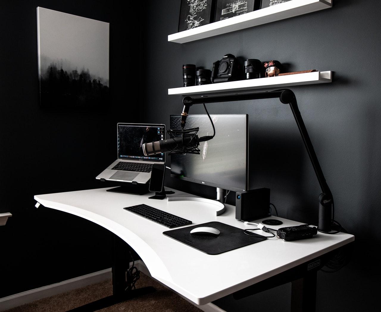 Imagem mostra uma mesa com um PC e um microfone montado em um pedestal.