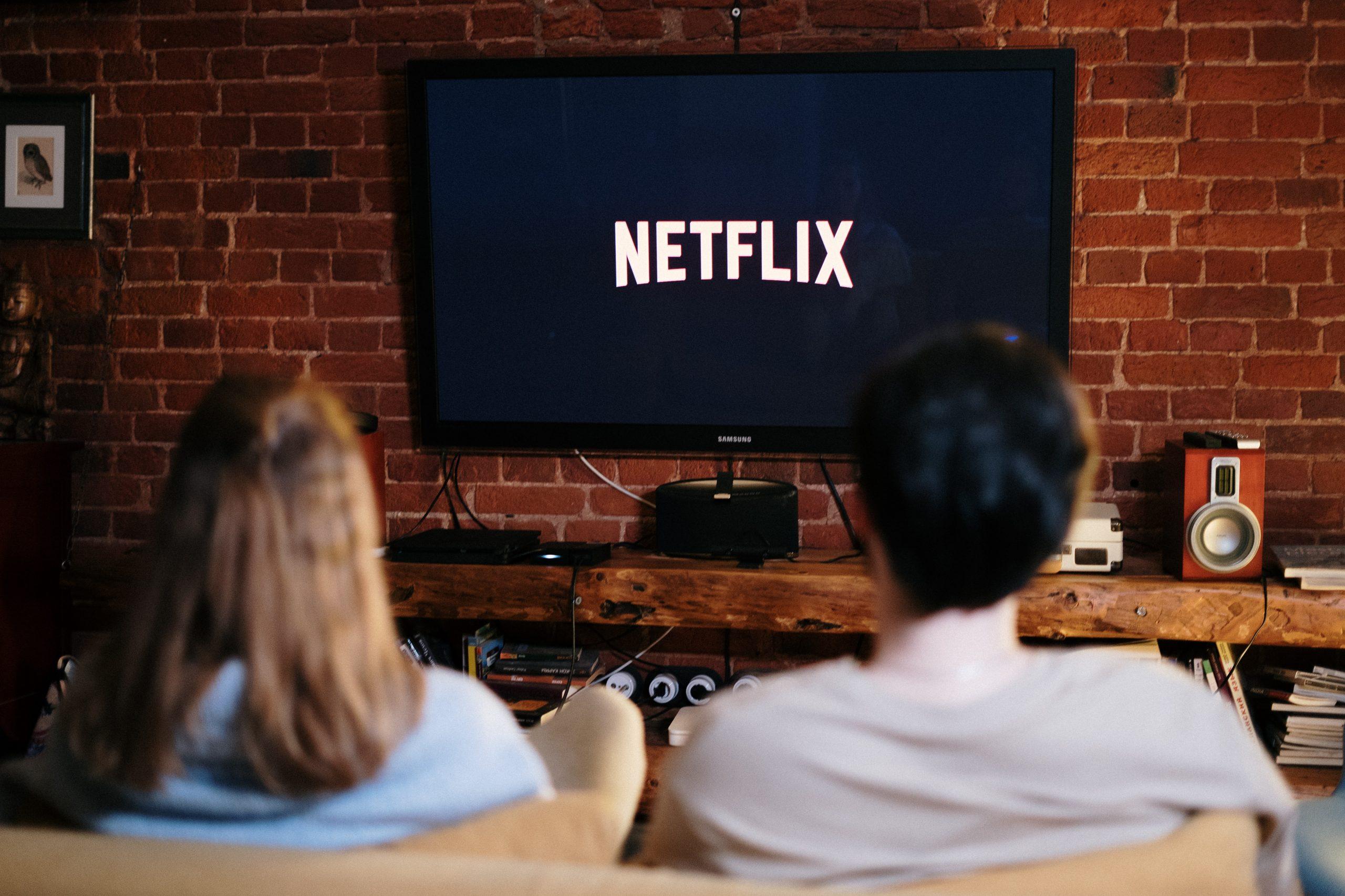 Imagem mostra um casal assistindo a uma televisão com Netflix.